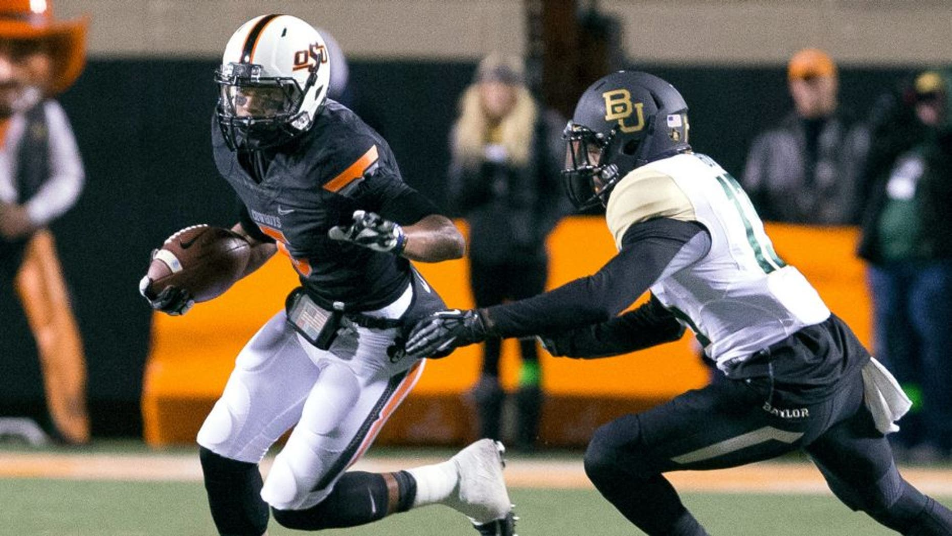 Nov 23, 2013; Stillwater, OK, USA; Oklahoma State Cowboys wide receiver Josh Stewart (5) runs the ball during the first quarter against Baylor Bears safety Terrell Burt (13) at Boone Pickens Stadium. Mandatory Credit: Richard Rowe-USA TODAY Sports