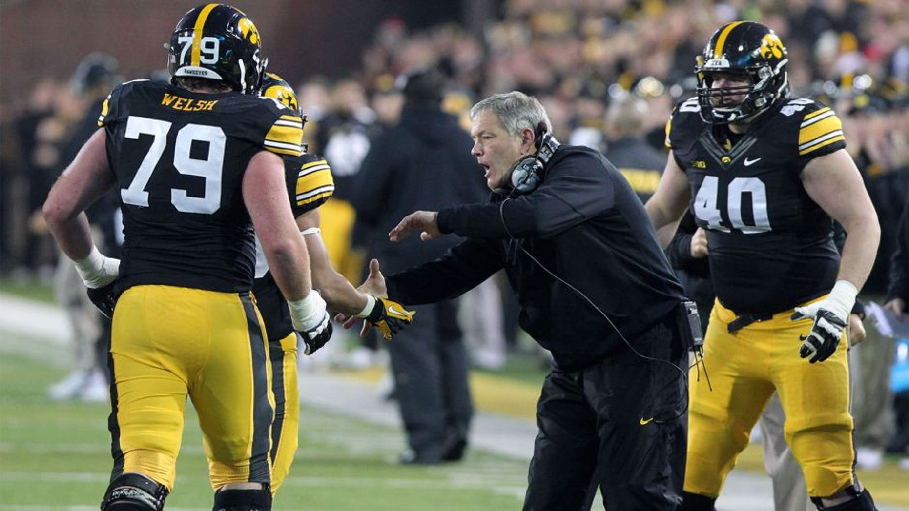Nov 22, 2014; Iowa City, IA, USA; Iowa Hawkeyes head coach Kirk Ferentz celebrates with offensive lineman Sean Welsh (79) after the Hawks scored a touchdown against the Wisconsin Badgers at Kinnick Stadium. Wisconsin beat Iowa 26-24. Mandatory Credit: Reese Strickland-USA TODAY Sports