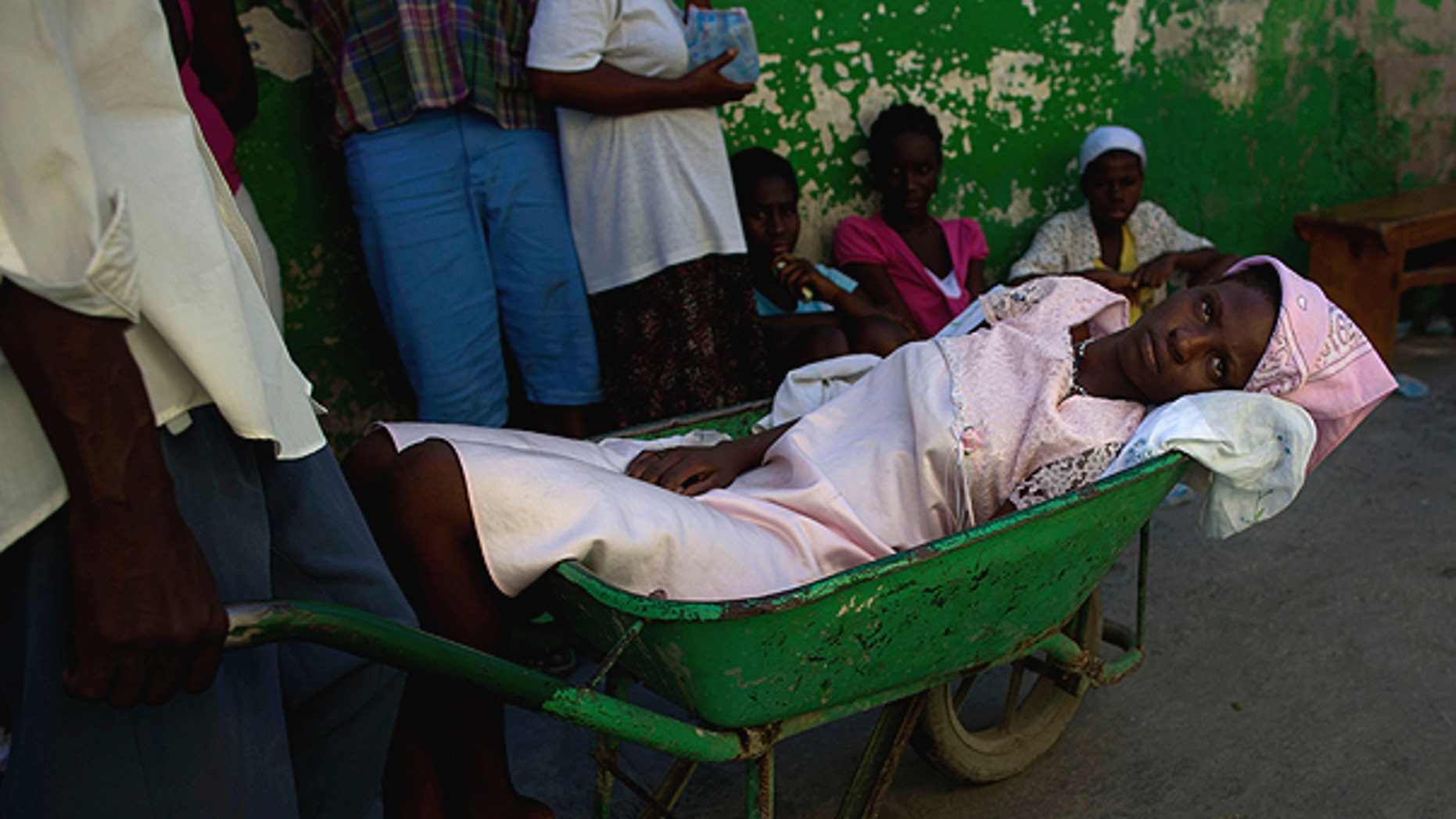 Nov. 17: A woman suffering cholera symptoms is pushed in a wheelbarrow to St. Catherine hospital, run by Doctors Without Borders, in the slum of Cite Soleil in Port-au-Prince, Haiti.