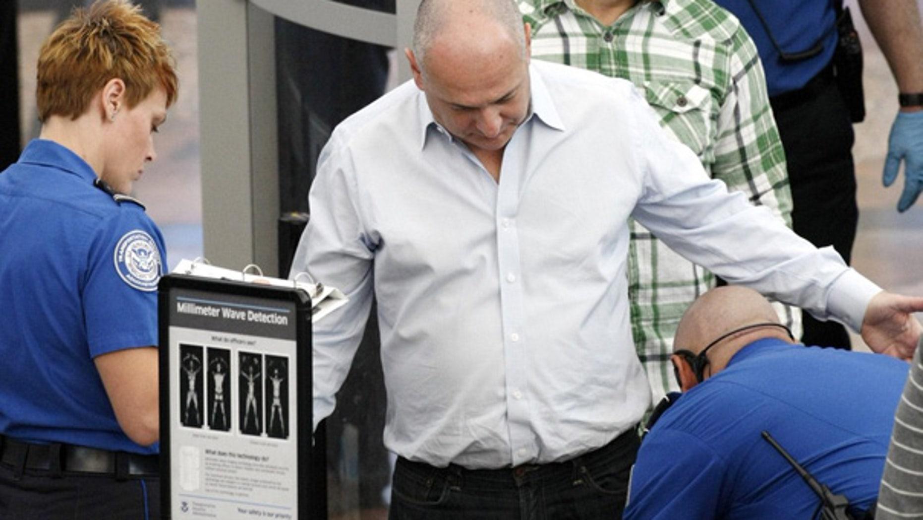 Nov. 23: A TSA worker rubs a traveler's leg as another TSA worker looks on during a pat-down at Denver airport.