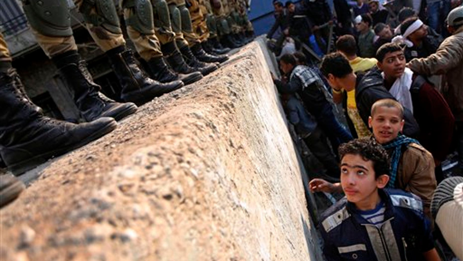 November 24, 2011: A boy looks at Egyptian Army soldiers standing guard atop a concrete block barricade on the street between Tahrir Square and the interior ministry in Cairo, Egypt.