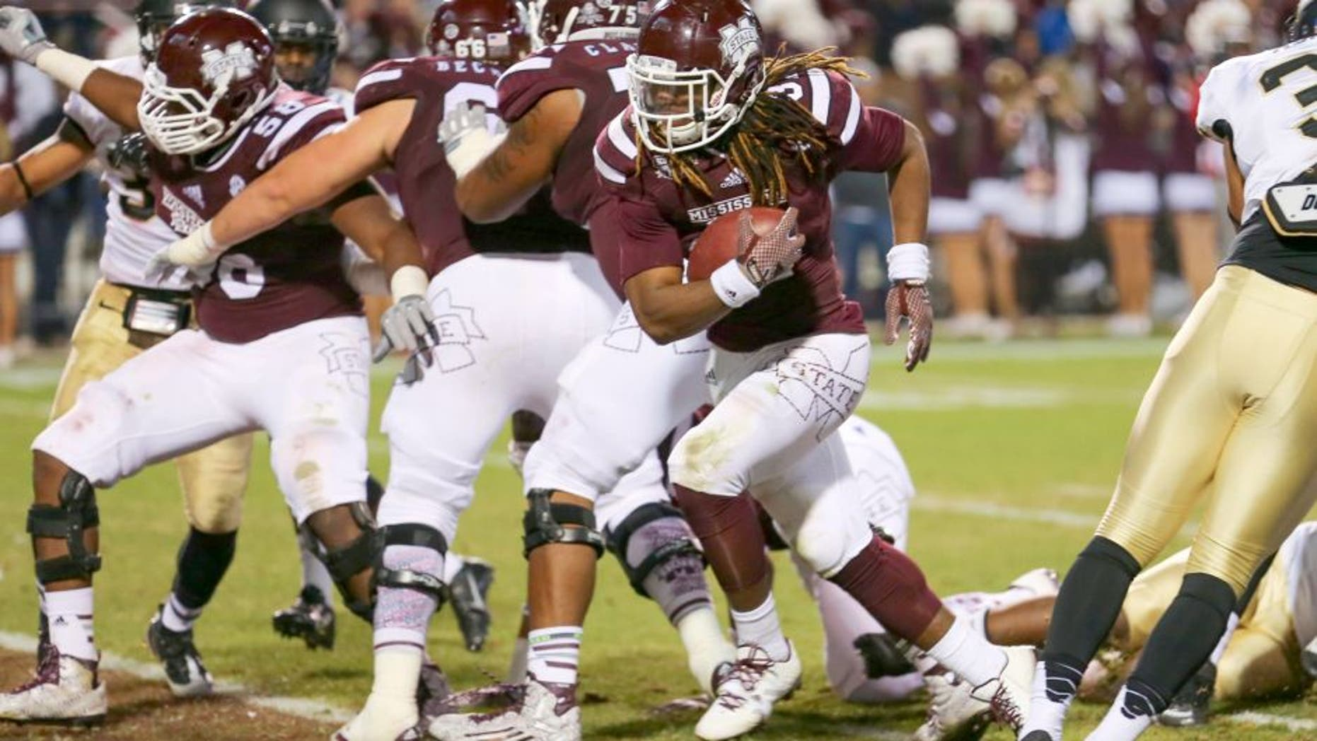 Nov 22, 2014; Starkville, MS, USA; Mississippi State Bulldogs running back Ashton Shumpert (32) carries the ball in for a touchdown during the game against the Vanderbilt Commodores at Davis Wade Stadium. Mandatory Credit: Spruce Derden-USA TODAY Sports