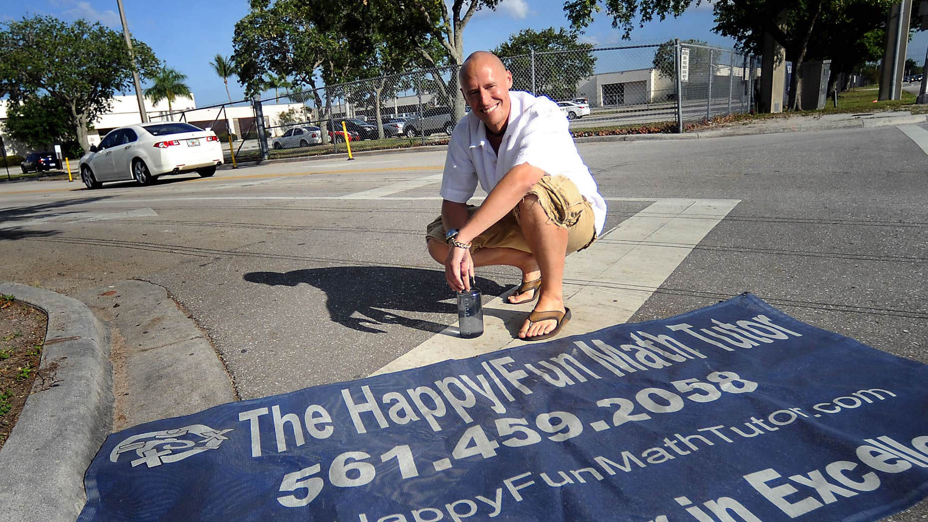In this 2013 photo, Dave Mech displays his sign that was taken down by three Boca Raton schools after a parent of a student looked into Mech's past and found that one of his companies was affiliated with adult entertainment.