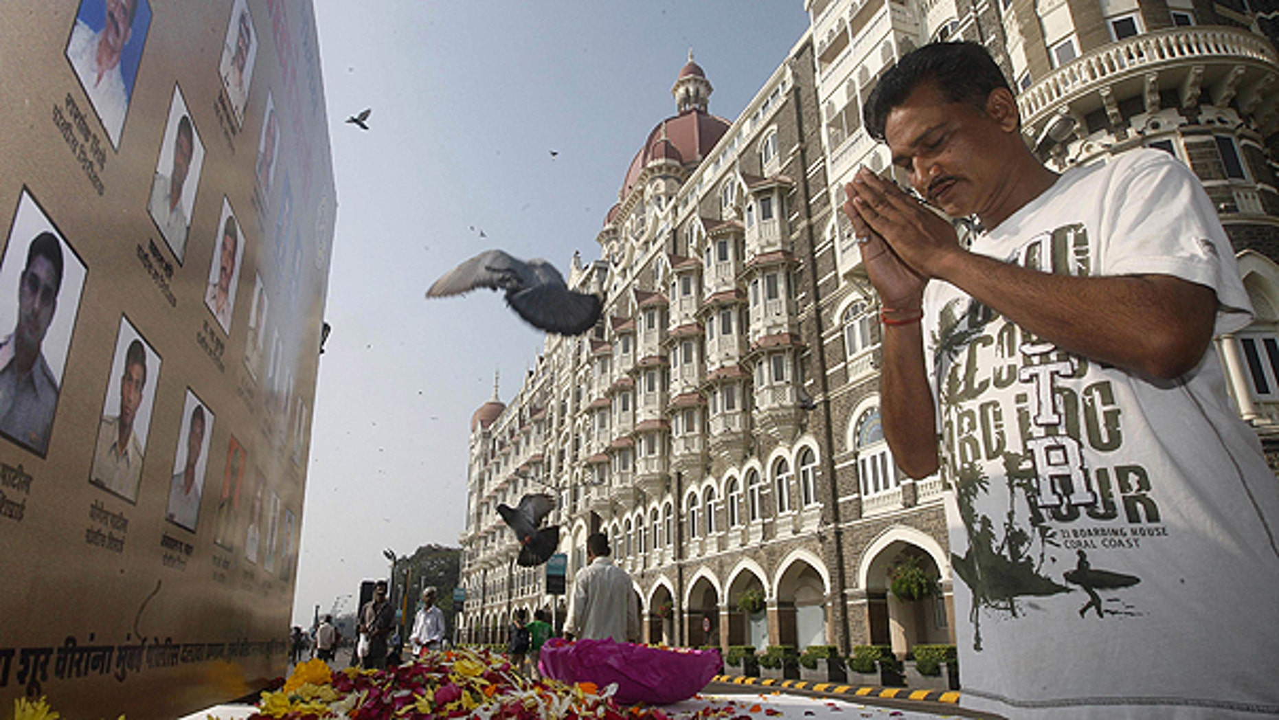 Nov. 26: A man pays homage in front of portraits of police officers killed in the Mumbai terror attack outside the Taj Mahal Palace hotel, one of the sites of the attack, on the second anniversary of the attack in Mumbai, India.