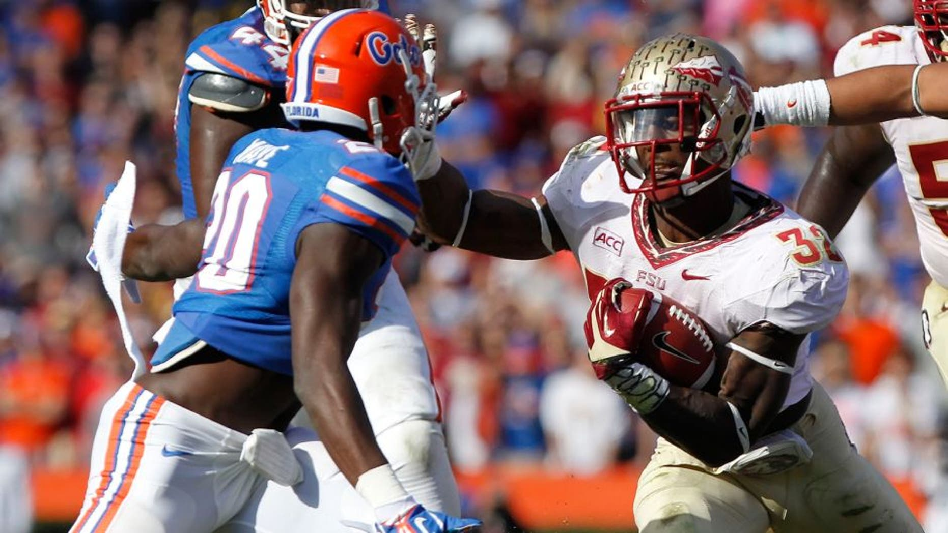 Nov 30, 2013; Gainesville, FL, USA; Florida State Seminoles running back James Wilder Jr. (32) runs with the ball as Florida Gators defensive back Marcus Maye (20) defends during the second half at Ben Hill Griffin Stadium. Florida State Seminoles defeated the Florida Gators 37-7. Mandatory Credit: Kim Klement-USA TODAY Sports