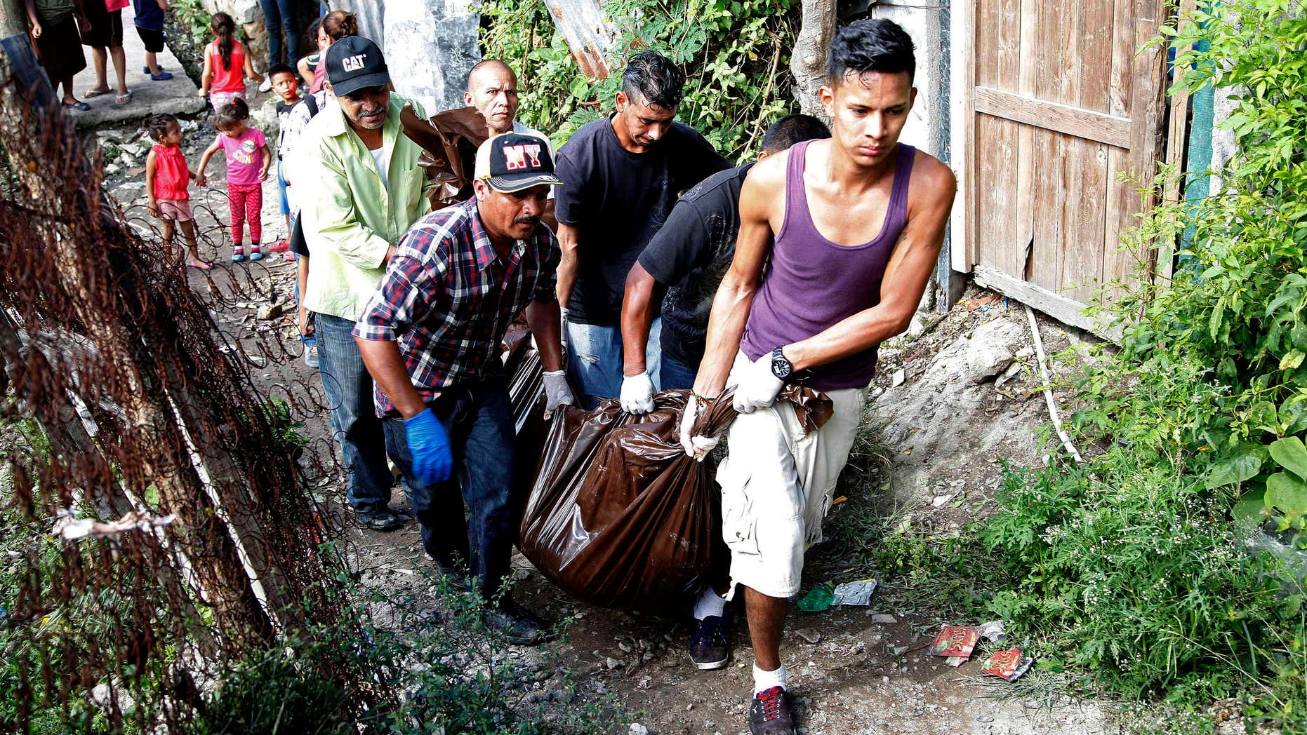 Nov. 25, 2015: A group of men help to remove bodies after armed young men pulled several men from their homes and executed them at a low income neighborhood in the capital city of Tegucigalpa, Honduras.