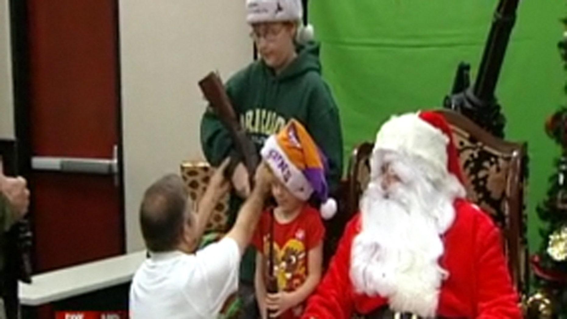 November 26, 2011: Children pose with Santa and guns at an Arizona gun club.