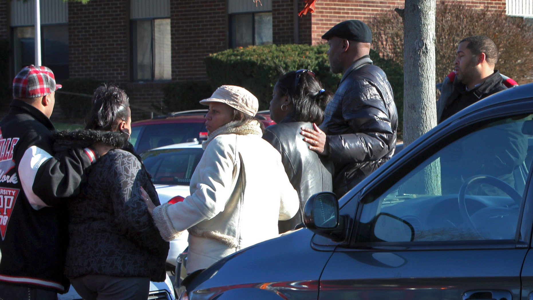 Nov. 26: Friends and co-workers of a woman involved in a triple homicide gather in the parking lot of her apartment complex on the north side of Columbus, Ohio.