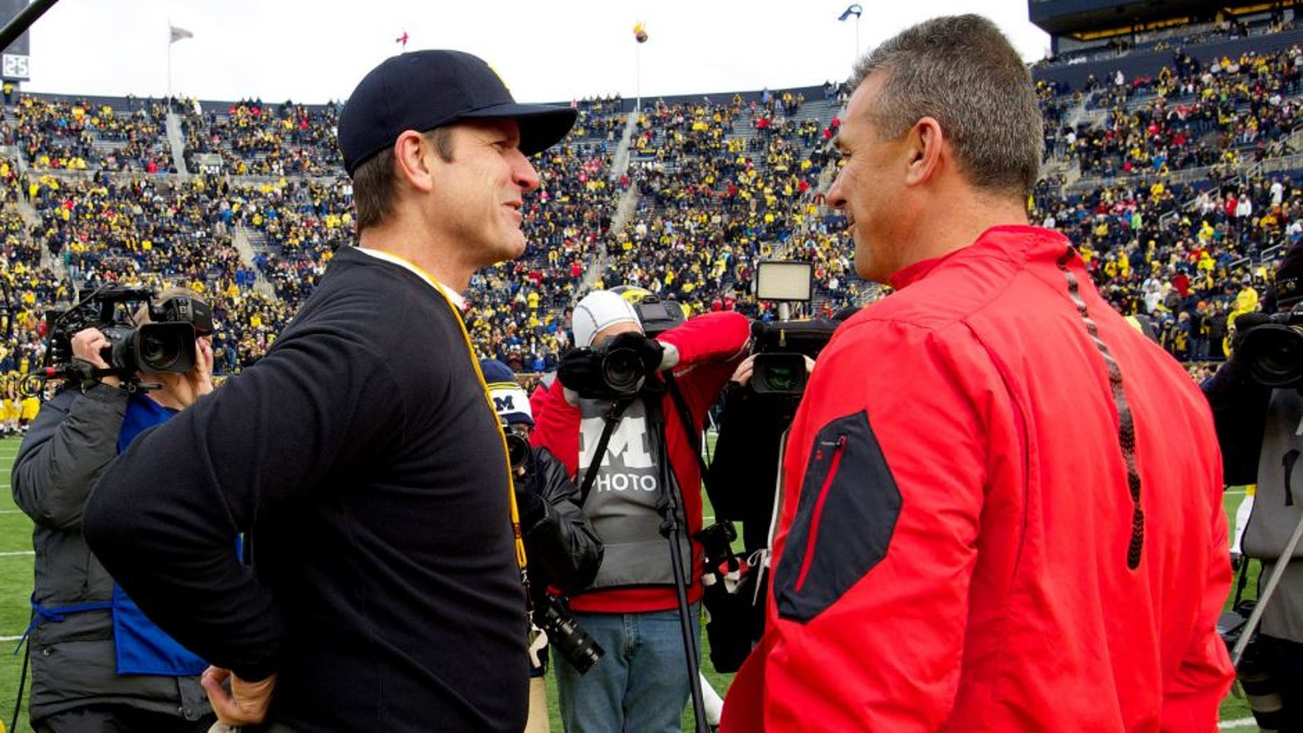 Michigan head coach Jim Harbaugh, left, talks with Ohio State head coach Urban Meyer, right, on the Michigan Stadium field before an NCAA college football game in Ann Arbor, Mich., Saturday, Nov. 28, 2015. (AP Photo/Tony Ding)