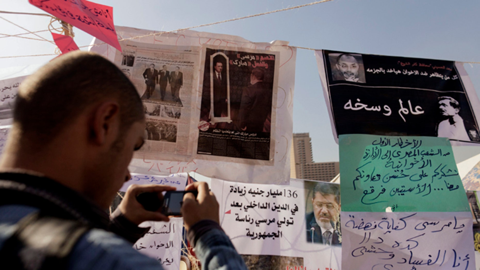 Nov. 29, 2012: An Egyptian protester photographs newspapers and placards on display in a makeshift museum in Tahrir Square in Cairo, Egypt.