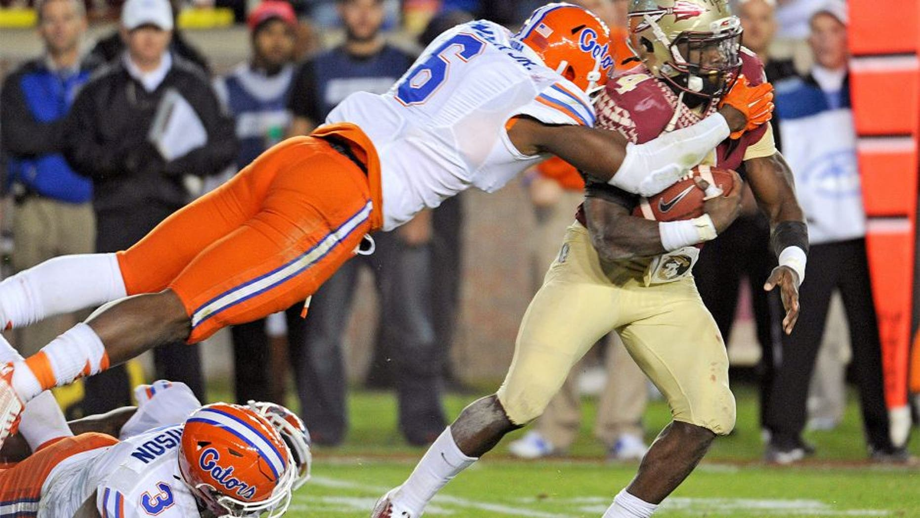 Nov 29, 2014; Tallahassee, FL, USA; Florida State Seminoles running back Dalvin Cook (4) runs the ball past Florida Gators defensive lineman Dante Fowler Jr. (6) and linebacker Antonio Morrison (3) during the game at Doak Campbell Stadium. Mandatory Credit: Melina Vastola-USA TODAY Sports