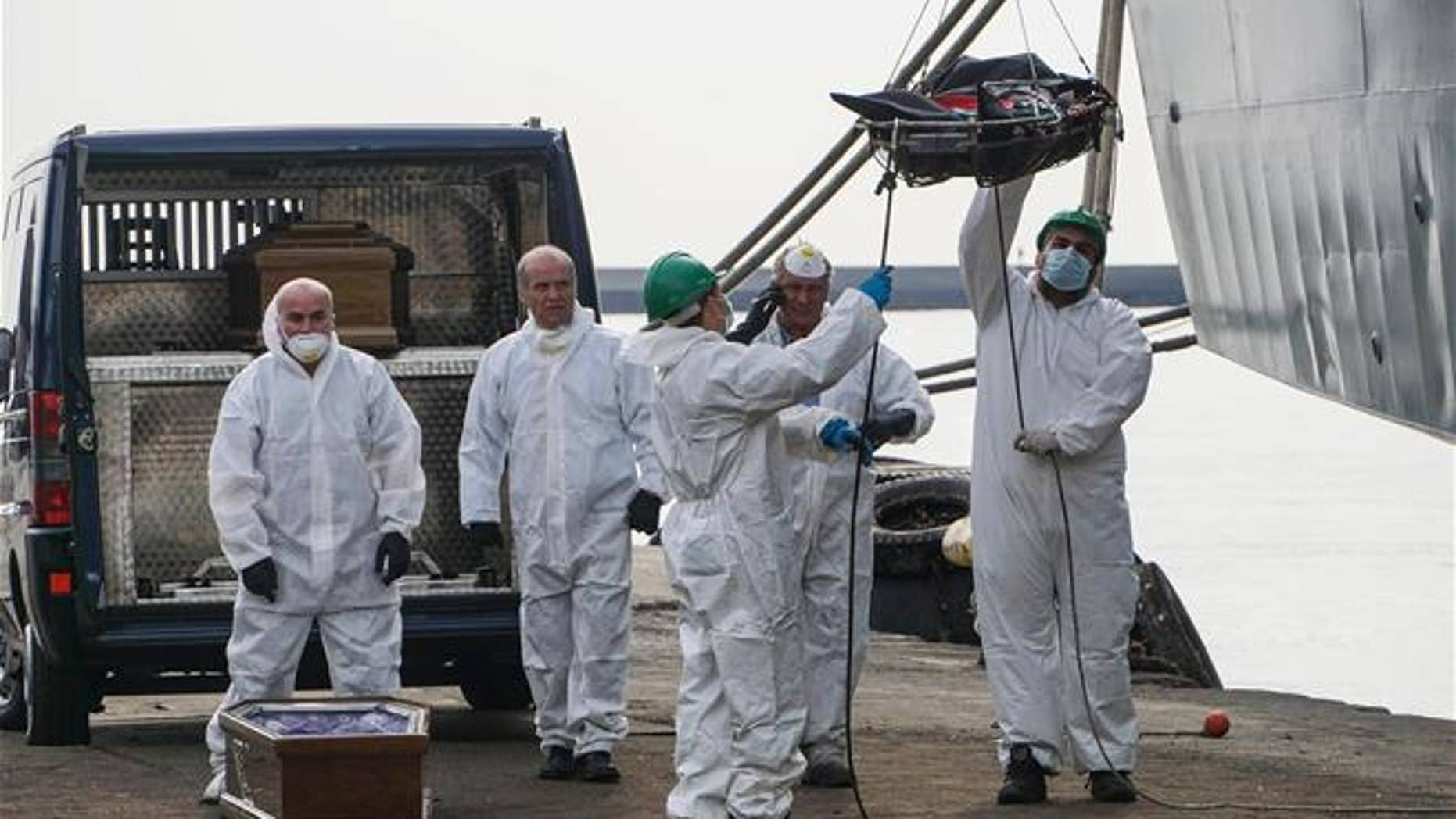 Rescuers recover a dead body from the Spanish ship 'Cantabria' in the harbour of Salerno, Italy, Sunday, Nov. 5 2017. UNHCR spokesman Marco Rotunno said that the 26 dead were involved in a shipwreck two days ago off Libya.