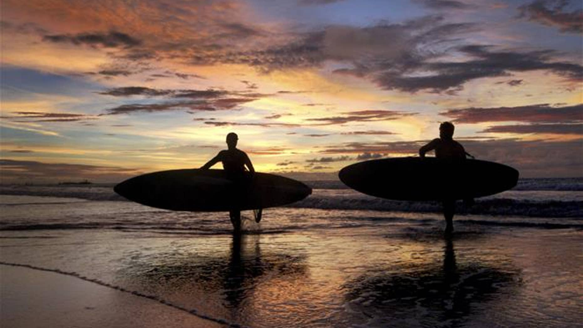 Two surfers carrying their boards are silhouetted against the sunset at Kuta Beach in Bali, Indonesia.