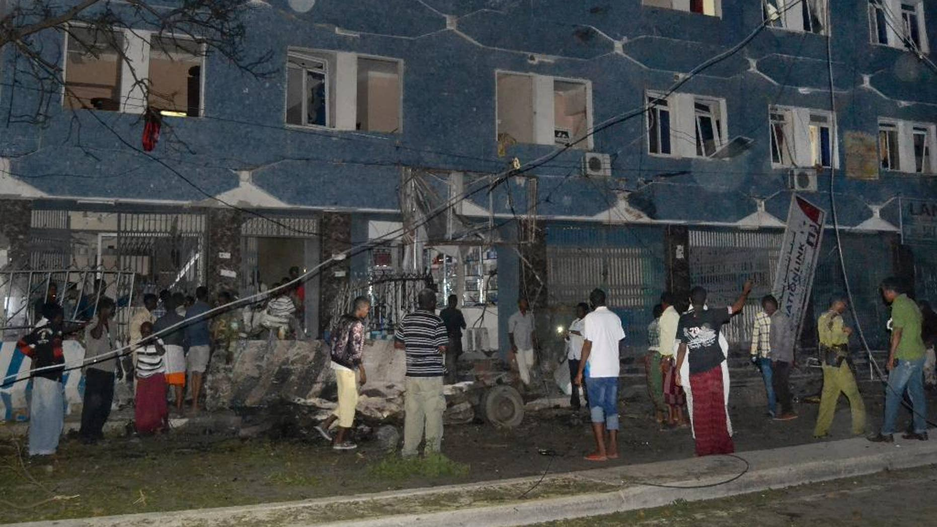 Somali security forces and civilians gather outside the Weheliye hotel after it was stormed by militants in Mogadishu, Somalia, Friday, July 10, 2015. Suspected Islamic militant gunmen stormed two hotels in Mogadishu, a Somali police official said Friday. (AP Photo)