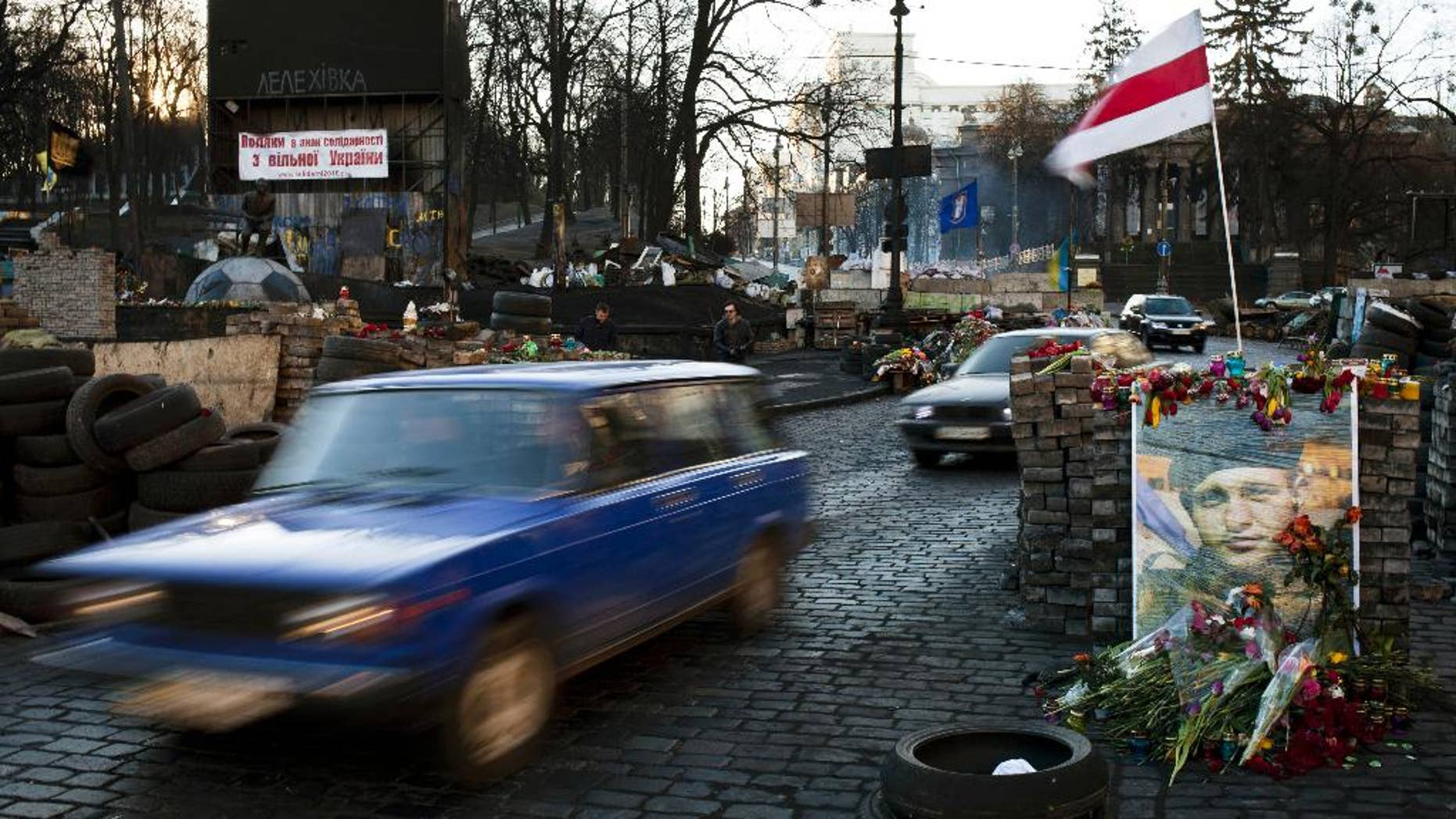 Cars make their way past barricades placed on a road near the Dynamo Kyiv soccer club stadium in Kiev, Ukraine, Wednesday, March 12, 2014. (AP Photo/David Azia)