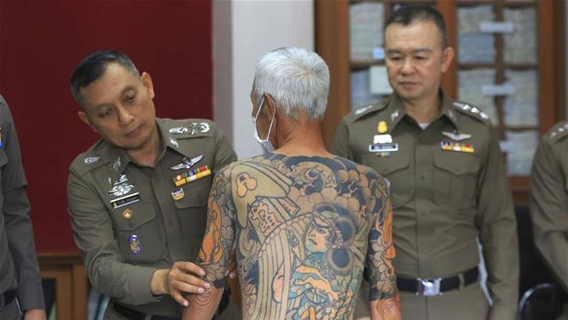 Japanese gang member Shigeharu Shirai displays his tattoos at a police station during a press conference in Lopburi.