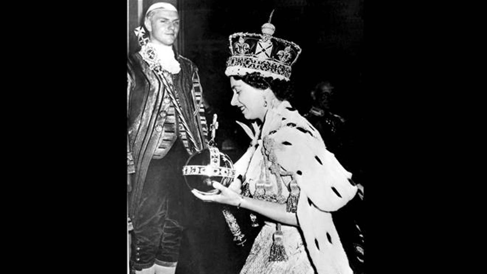 In this 1953 file photo, Britain's Queen Elizabeth II, wearing the bejeweled Imperial State Crown and carrying the Orb and Scepter with Cross, leaves Westminster Abbey in London at the end of her coronation ceremony.