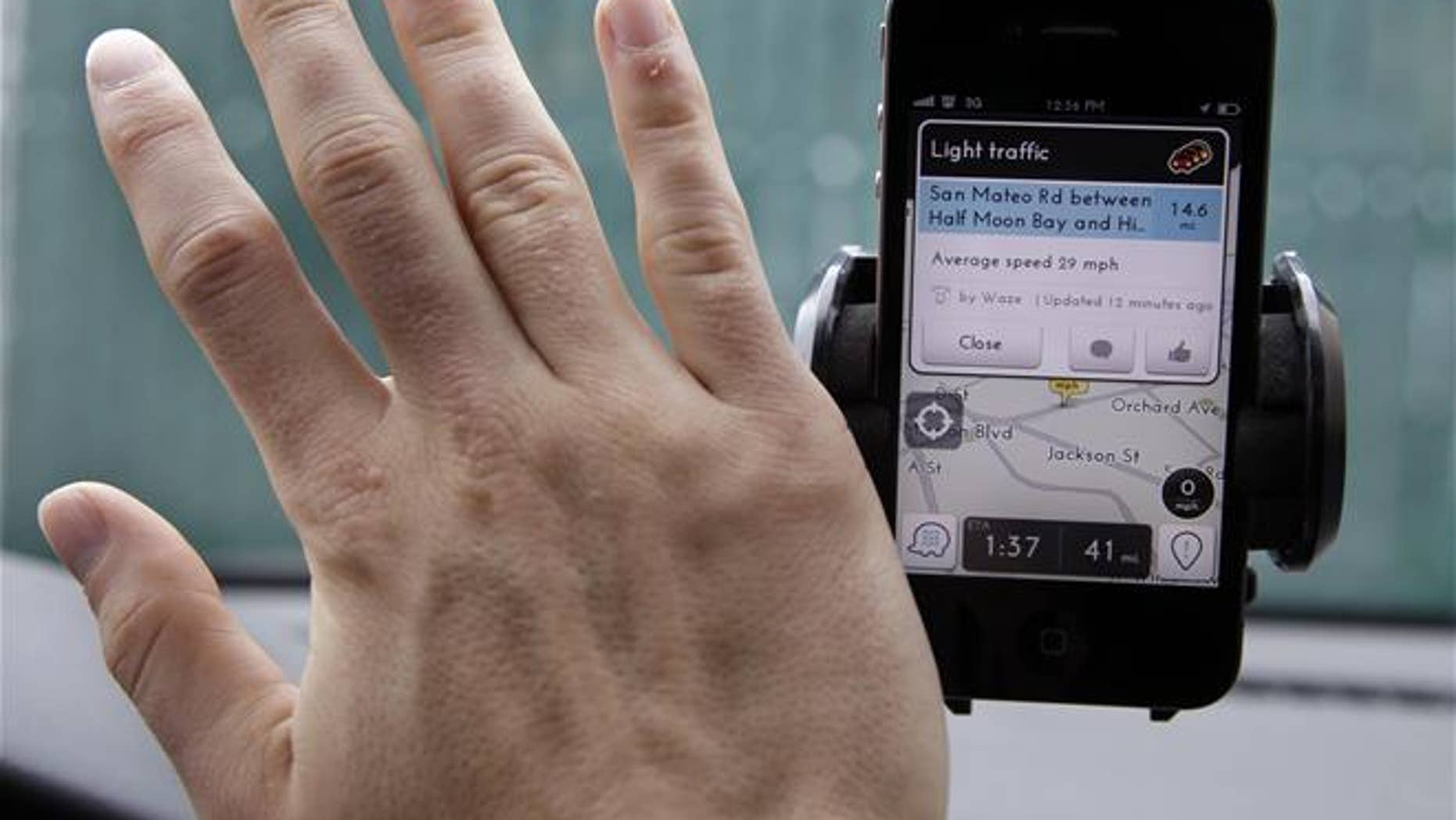 In this March 15, 2012, file photo, a user waves his hand over the Waze traffic and navigation app on his Apple iPhone in a Menlo Park, Calif., parking lot.