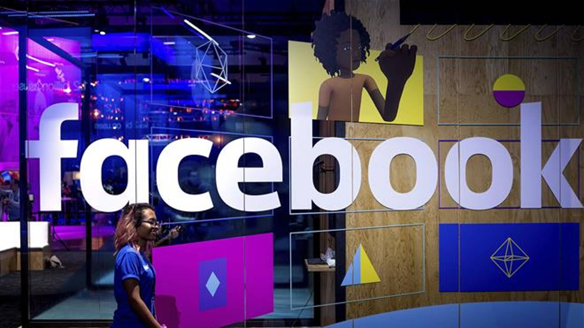 In this Tuesday, April 18, 2017, file photo, a conference worker passes a demo booth at Facebook's annual F8 developer conference, in San Jose, Calif. Facebook Inc. reports earnings Wednesday, Jan. 31, 2018.