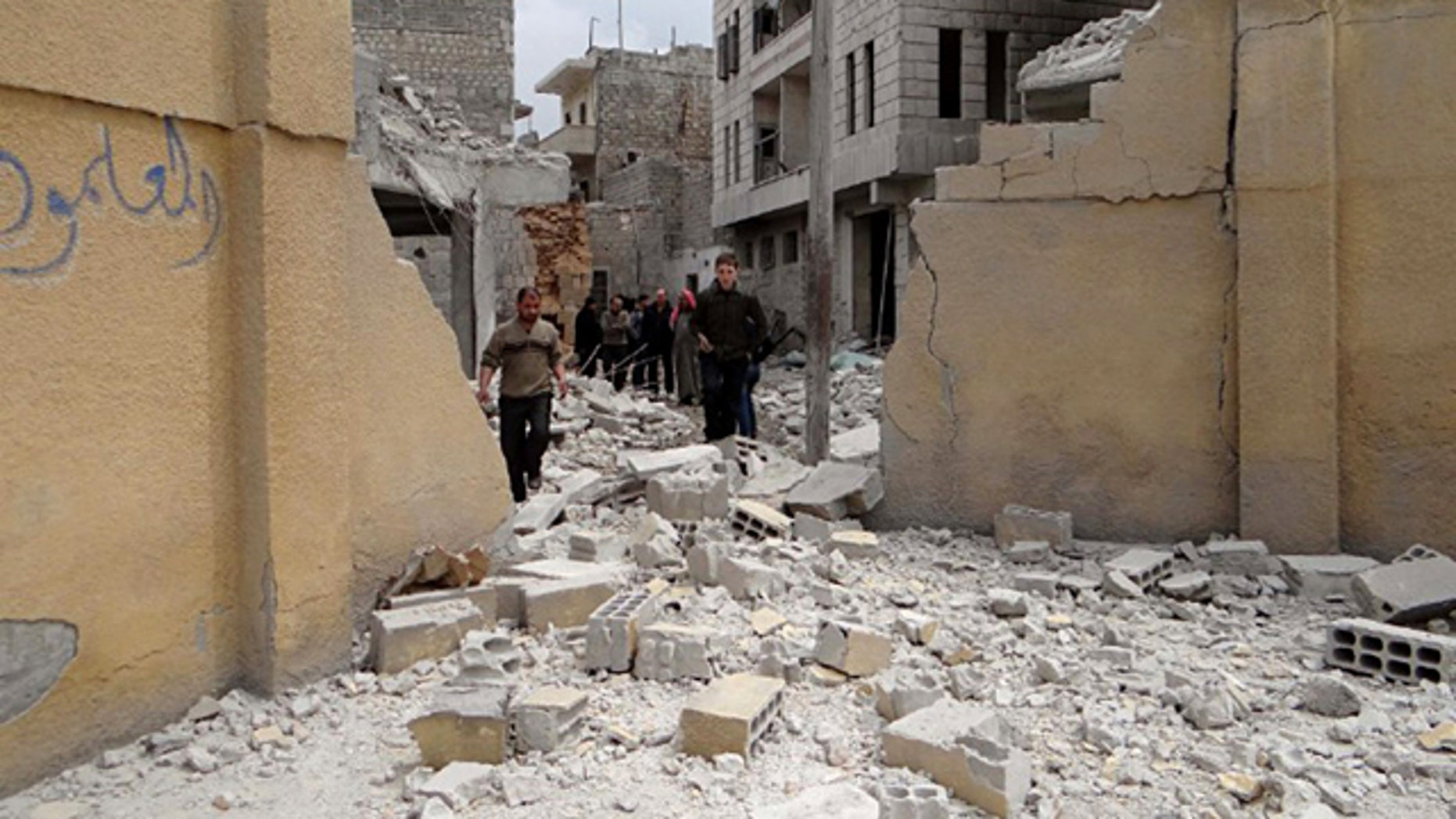 April 12, 2015: This photo posted by the anti-government activist website of the Syrian Observatory for Human Rights, which has been verified and is consistent with other AP reporting, shows Syrians walking at the damaged backyard of a school after an airstrike, in Ansari neighborhood in Aleppo. (Website of the Syrian Observatory for Human Rights via AP)