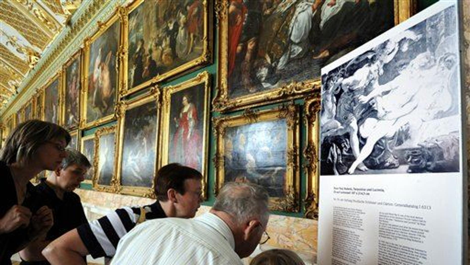 "Visitors look at a photo of a missing painting by Peter Paul Rubens entitled ""Tarquinius and Lucretia"" in the Gallery of Sanssouci in Potsdam, Germany,  in 2008. A different Rubens has now surfaced."