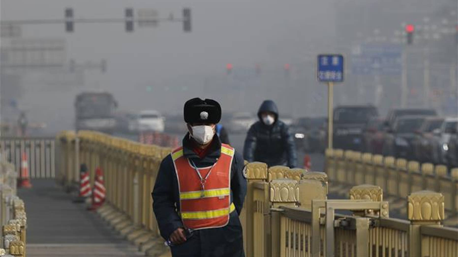 A traffic warden wearing a protection mask walks on a street near Tiananmen Square in Beijing as the capital of China is blanketed by heavy smog in this file photo.