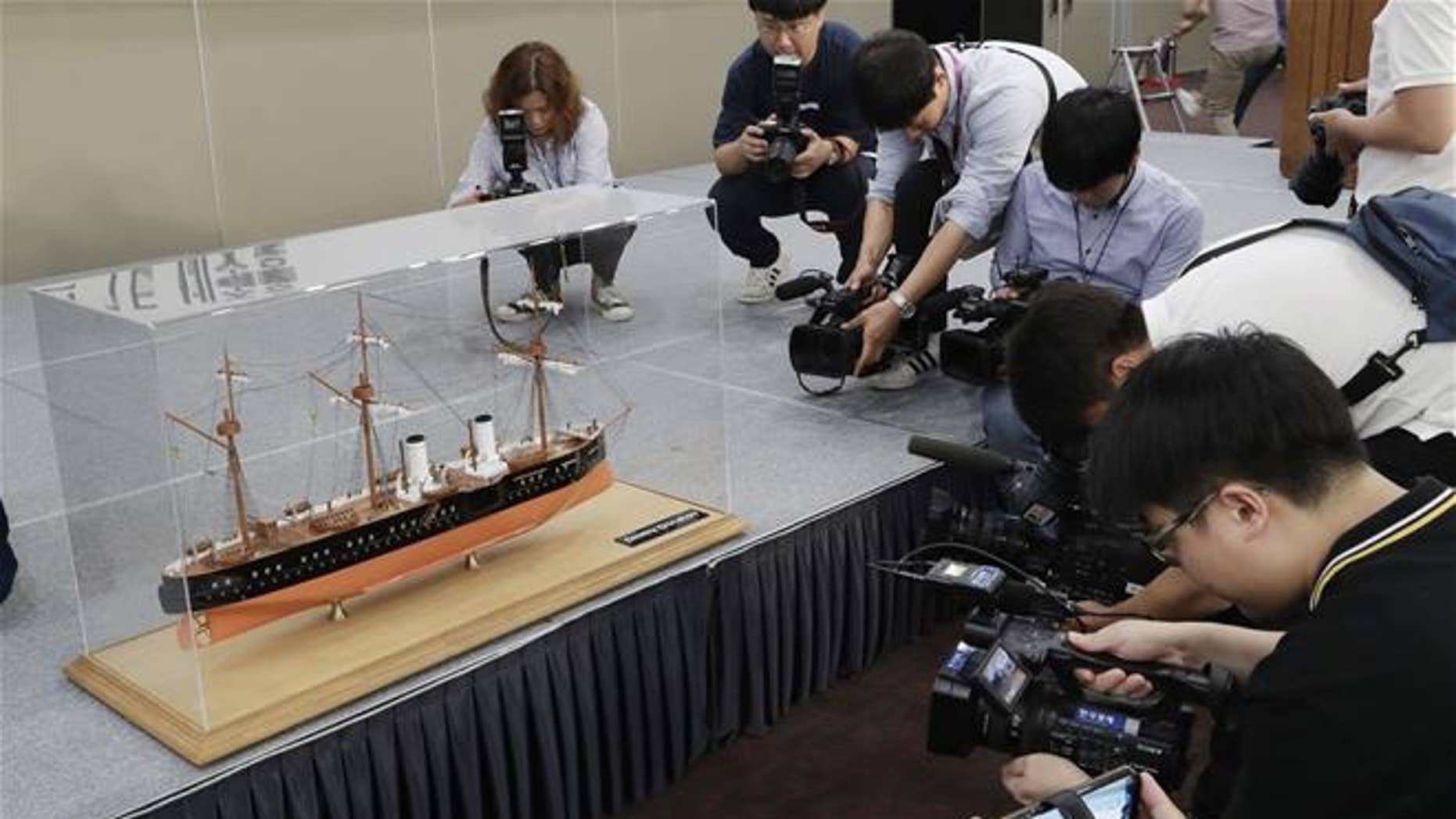 A scale model of the Russian warship Dmitrii Donskoi is surrounded by the media before a news conference in Seoul, South Korea, Thursday, July 26, 2018.