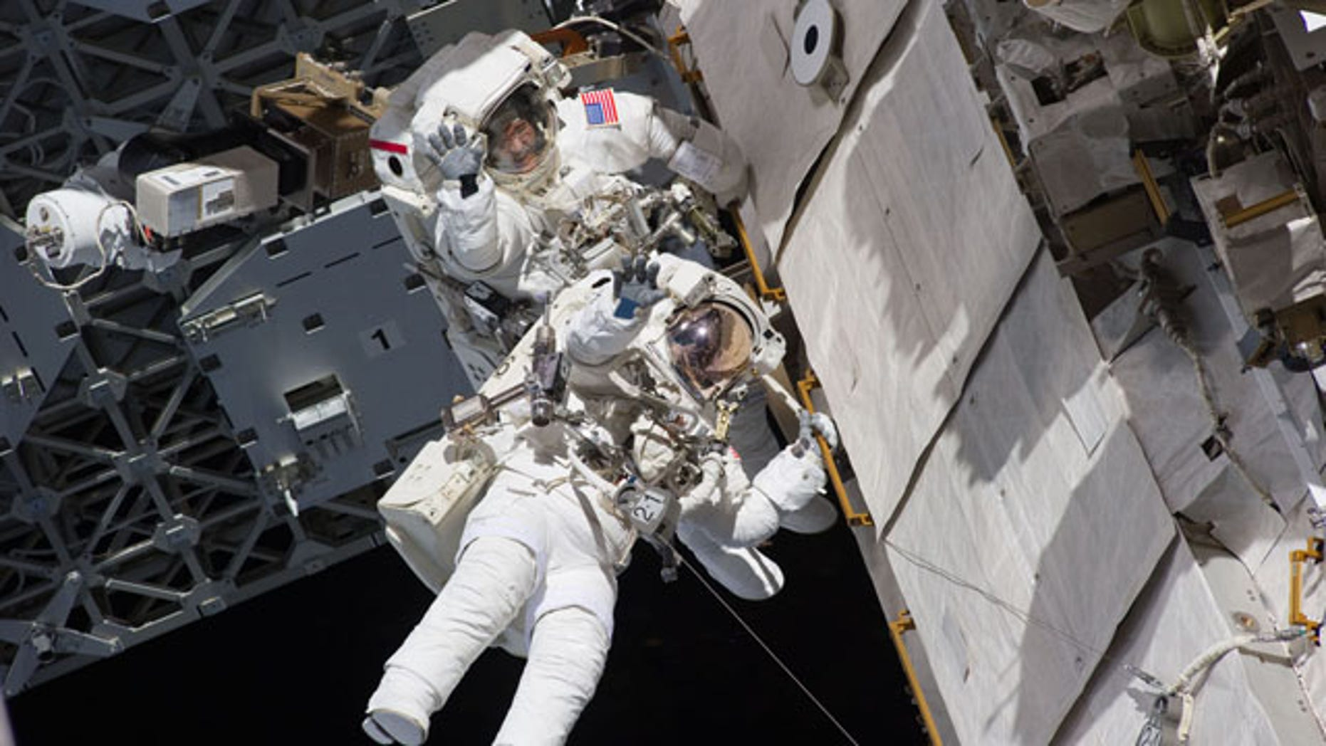 Astronauts Steve Bowen and Alvin Drew wave during the first spacewalk of their STS-133 mission on Feb. 28, 2011 while working outside the International Space Station during the final flight of space shuttle Discovery.