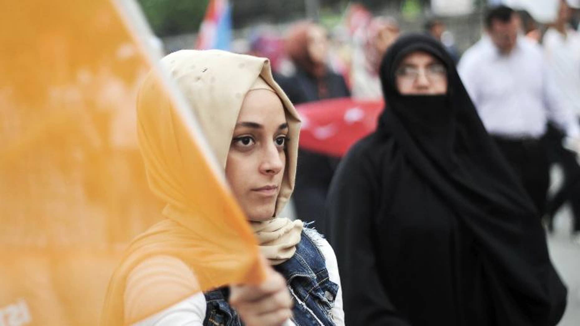 A supporter of Turkish Prime Minister Recep Tayyip Erdogan holds an AKP 'Justice and Development' party flag during a rally in Istanbul on June 16, 2013
