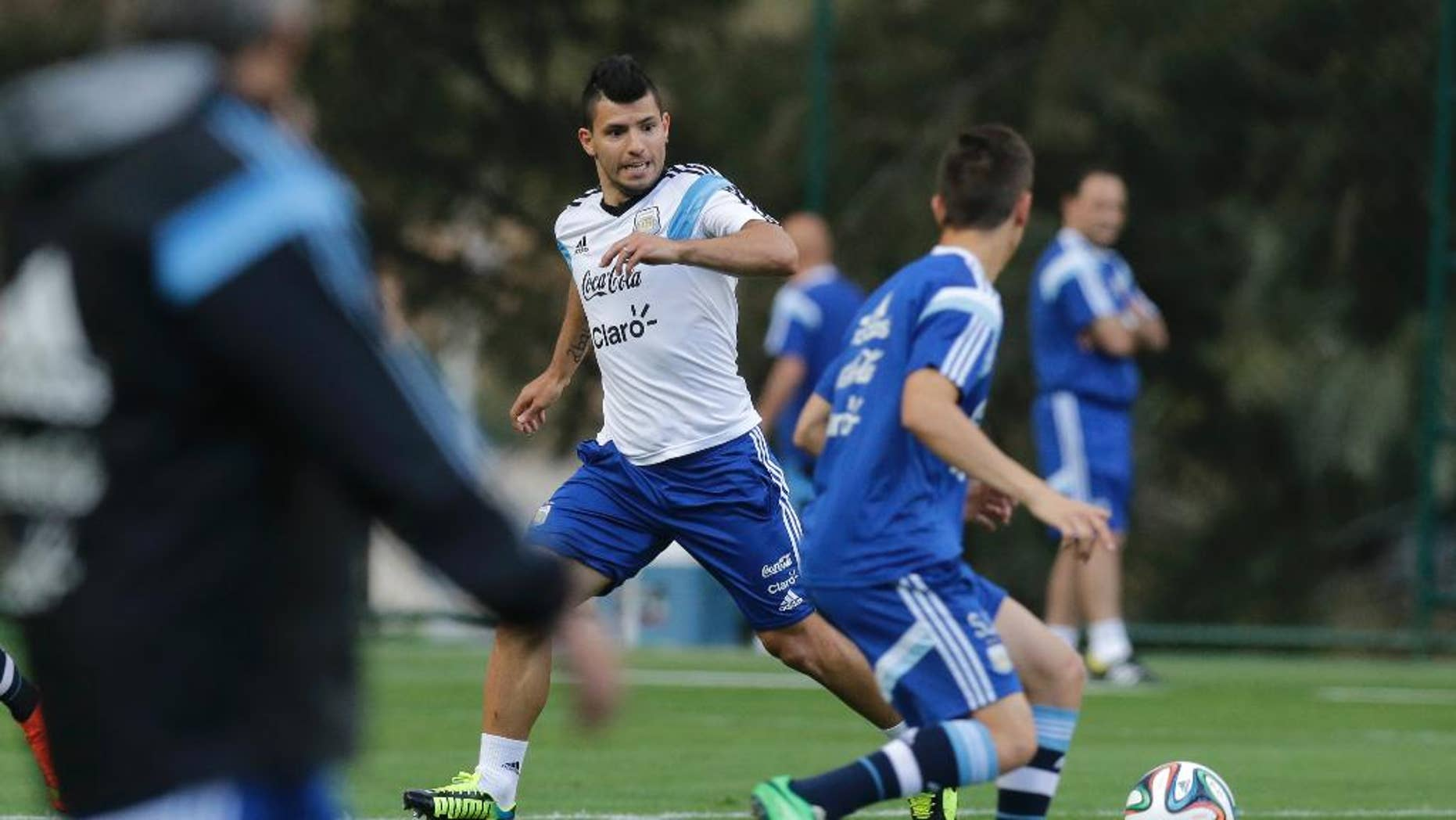 Argentina's Sergio Aguero, center, runs for the ball during a training session in Vespesiano, near Belo Horizonte, Brazil, Thursday, July 10, 2014. On Sunday, Argentina faces Germany for the World Cup final soccer match in Rio de Janeiro. (AP Photo/Victor R. Caivano)