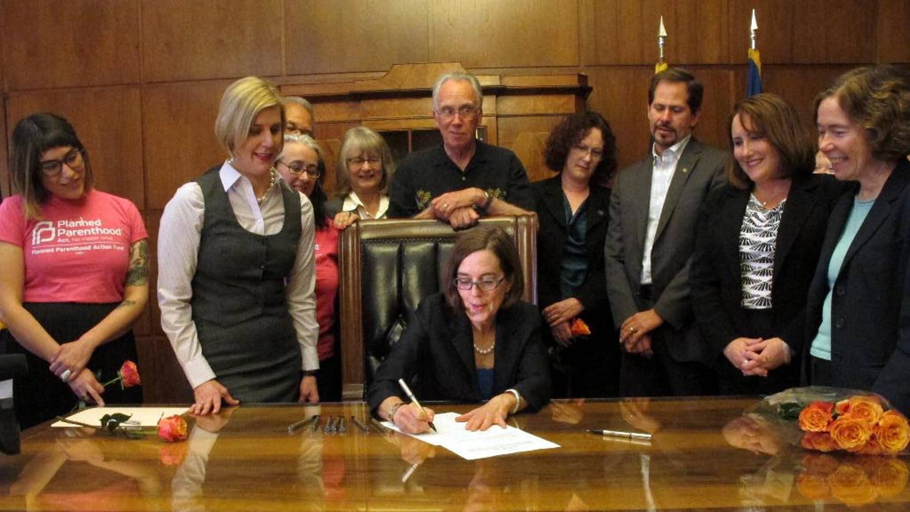 Gov. Kate Brown signs a bill expanding access to contraception during a ceremony at the state Capitol in Salem, Ore., on Thursday, June 11, 2015. The bill makes Oregon the first state to require insurers to pay for up to 12 months of birth control at a time. (AP Photo/Jonathan J. Cooper)