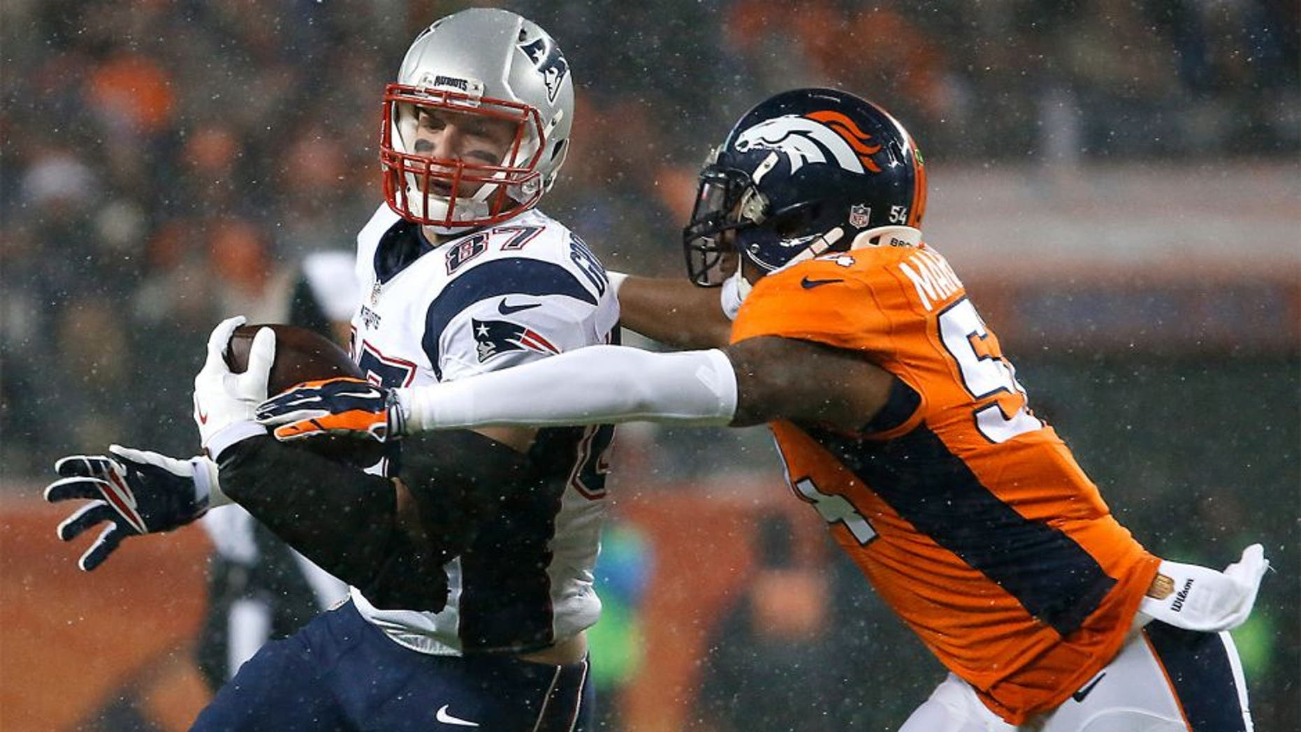 DENVER, CO - NOVEMBER 29: Patriots tight end Rob Gronkowski looks up field, picking up additional yardage after a catch before the Broncos' Brandon Marshall moved in for a tackle during first quarter action. The Denver Broncos hosted the New England Patriots for a regular season NFL game at Sports Authority Field at Mile High on Sunday, Nov. 29, 2015. (Photo by Matthew J. Lee/The Boston Globe via Getty Images)