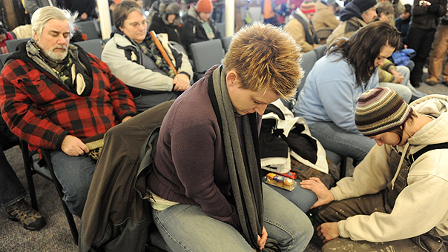 Dec. 2: Tina VanDerMade, center, from Sherwood, Ohio and Tracy Robertson, right, from Montpelier, Ohio, bow their heads in prayer at the Morenci Bible Fellowship Church, before going out with volunteers to continue the search for 9-year-old Andrew, 9, Alexander, 7 and Tanner Skelton, 5 in Morenci, Mich.