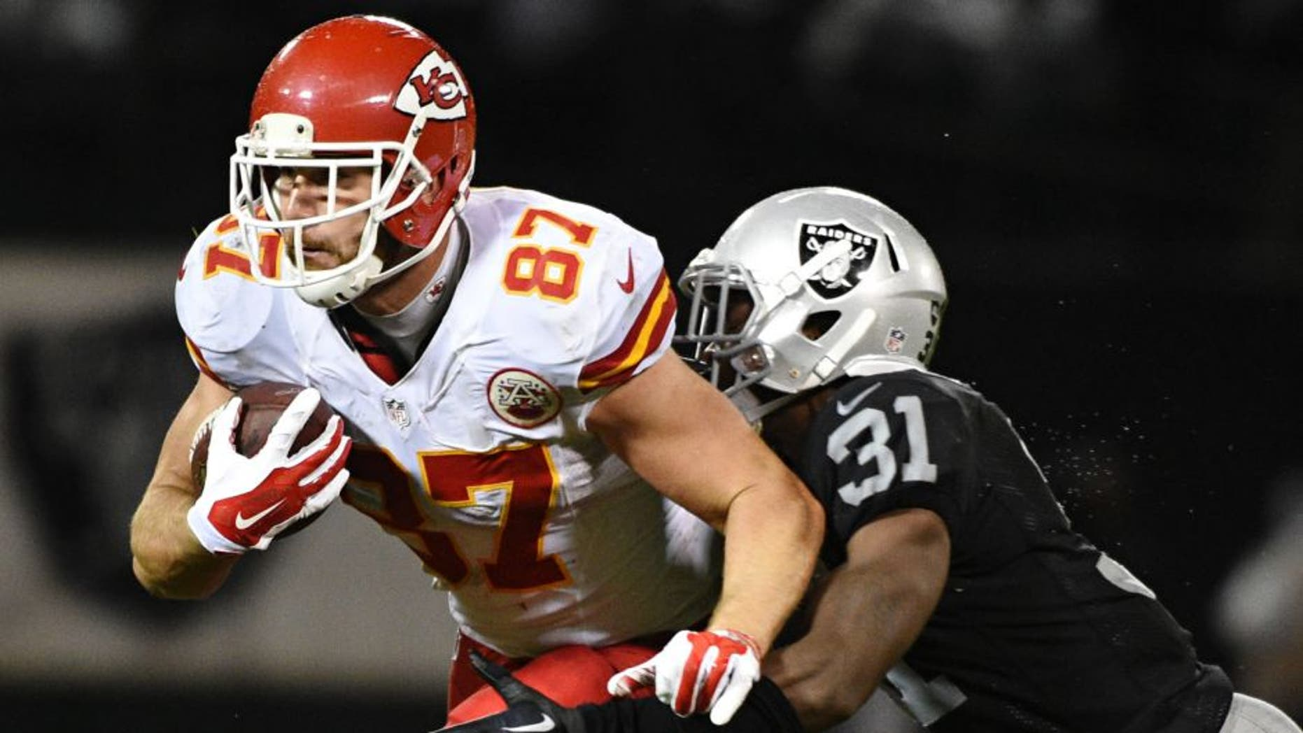 November 20, 2014; Oakland, CA, USA; Kansas City Chiefs tight end Travis Kelce (87) is tackled by Oakland Raiders defensive back Neiko Thorpe (31) during the third quarter at O.co Coliseum. The Raiders defeated the Chiefs 24-20. Mandatory Credit: Kyle Terada-USA TODAY Sports