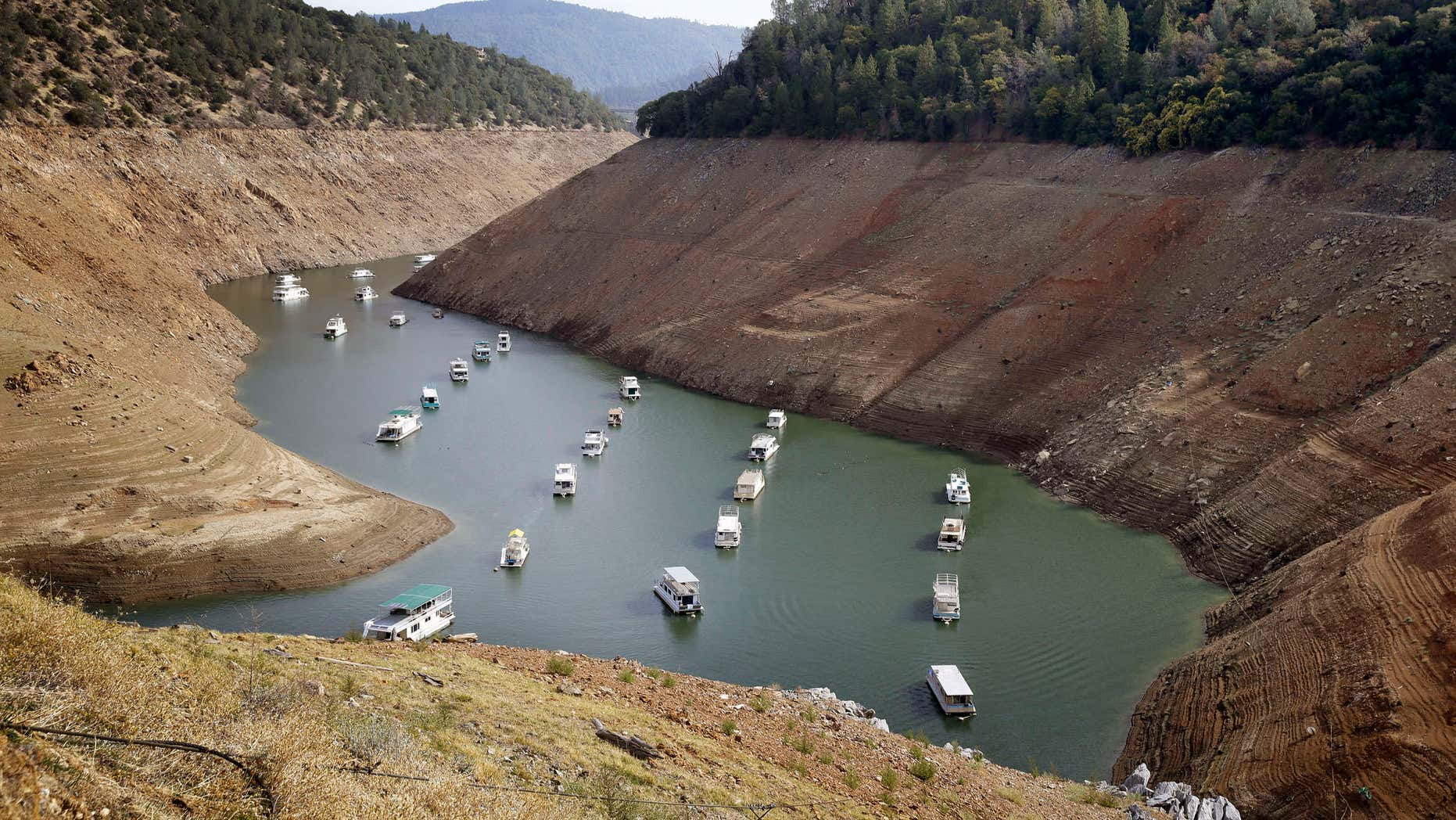 FILE - In this Thursday, Oct. 30, 2014, file photo, houseboats float in the drought-lowered waters of Oroville Lake near Oroville, Calif.