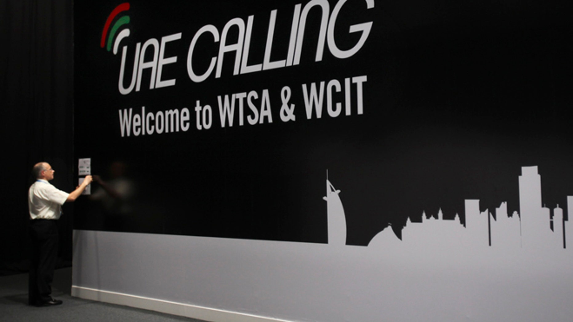 Dec. 3, 2012: An official sticks a note on the wall next to the conference banner during the eleventh day of the World Conference on International Telecommunication in Dubai, United Arab Emirates.