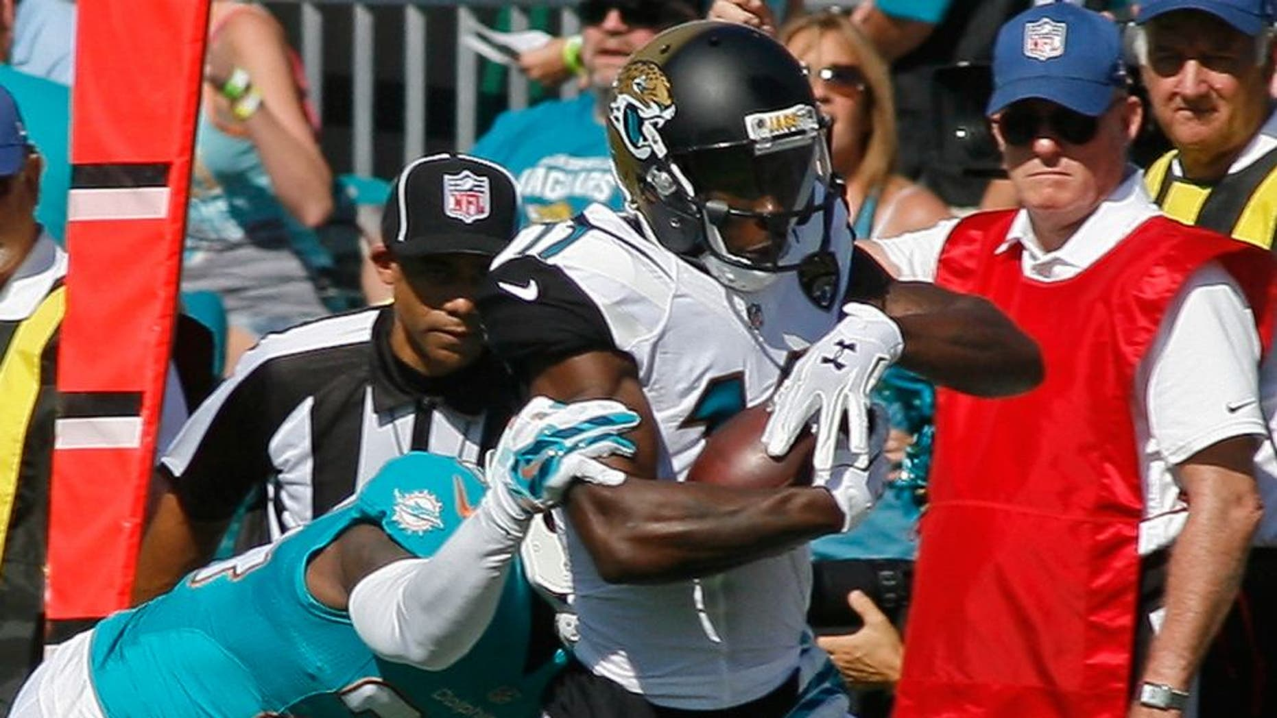 Sep 20, 2015; Jacksonville, FL, USA; Jacksonville Jaguars wide receiver Marqise Lee (11) tries to get by Miami Dolphins cornerback Brice McCain (24) on his first NFL catch in the first quarter at EverBank Field. Mandatory Credit: Phil Sears-USA TODAY Sports