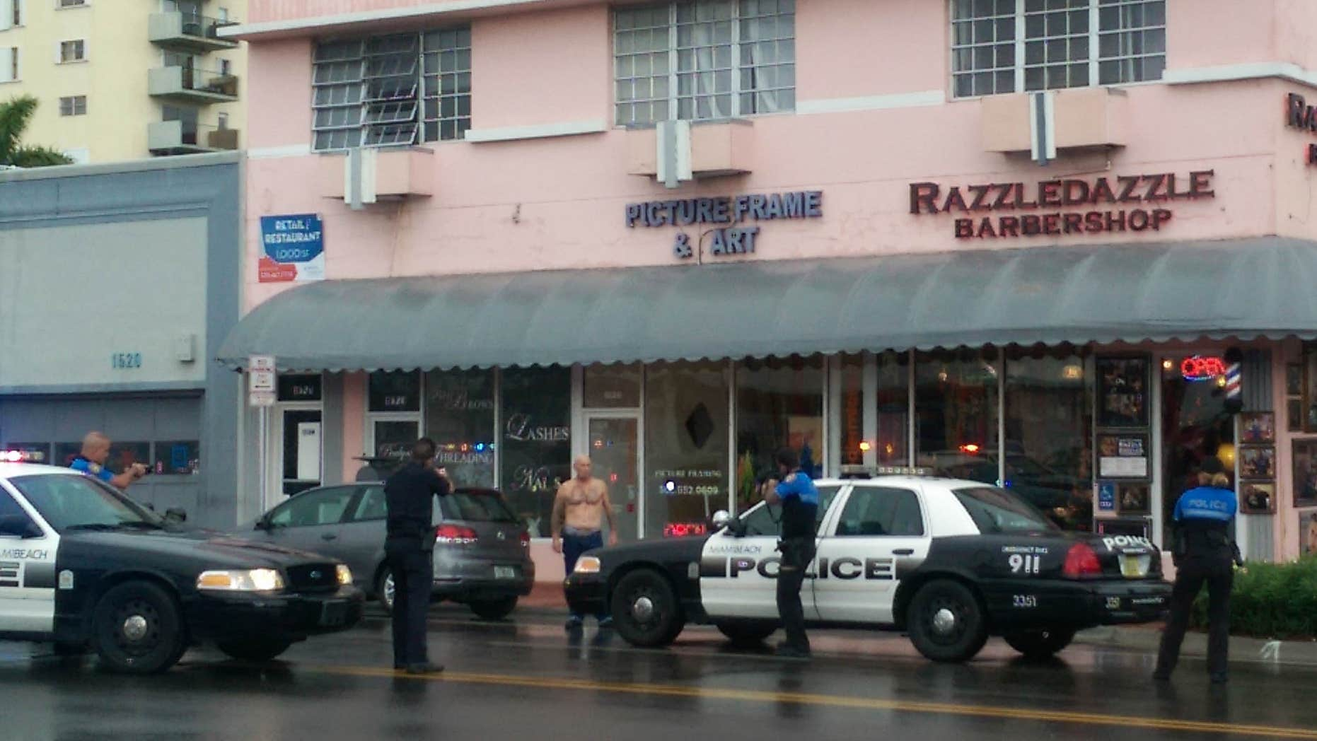 Dec. 5, 2015: In this photo provided by Marcellus Johnson, authorities draw their guns on a man suspected in a bank robbery in Miami Beach, Fla.