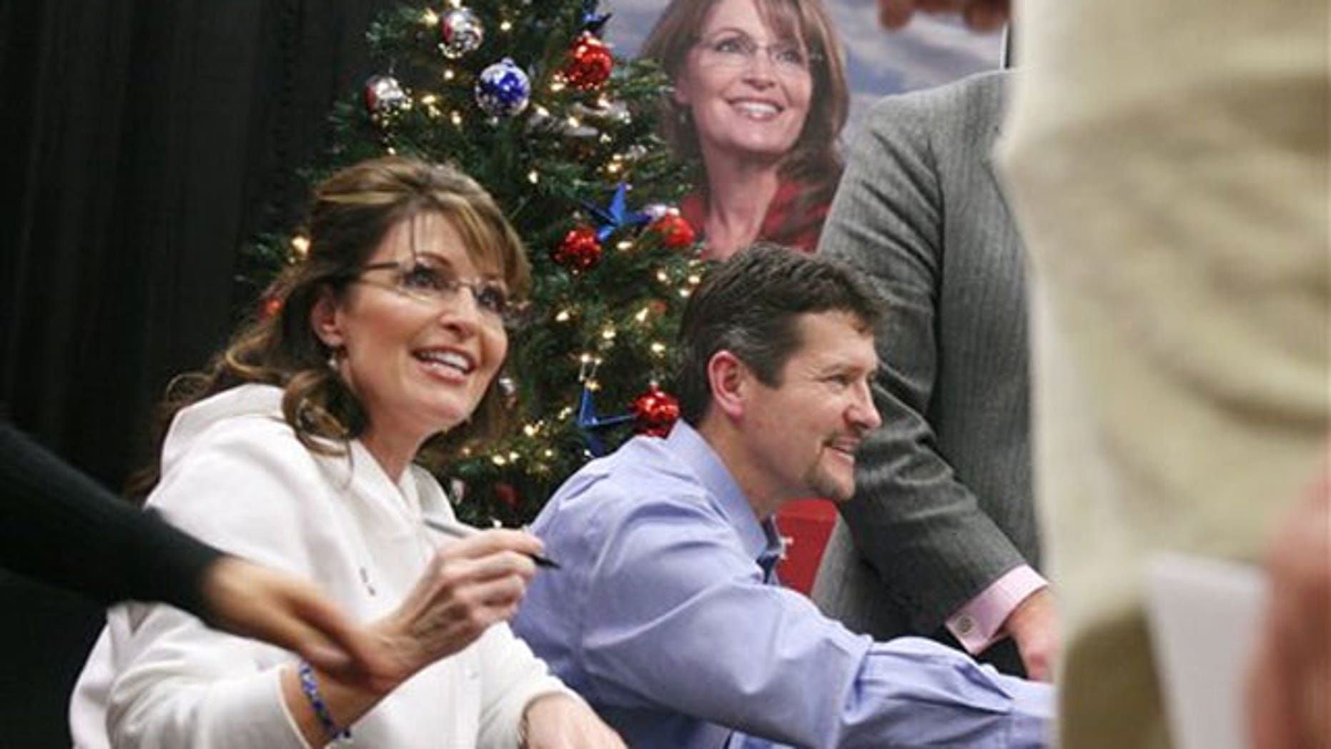 Dec. 4: Sarah Palin, left, signs her book 'Going Rogue' with help from her husband, Todd, in Fort Hood, Texas (AP).