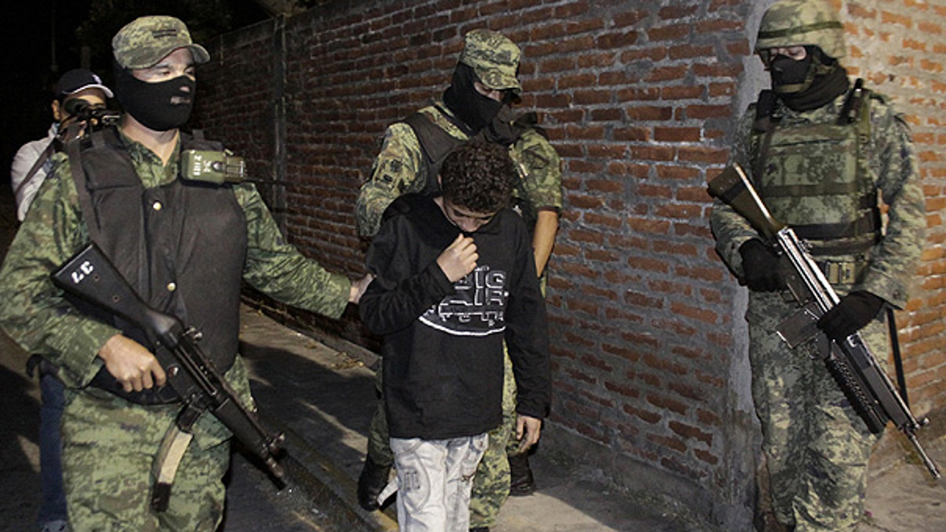 "Dec. 3: Soldiers escort a 14-year-old known as ""El Ponchis"" who is suspected of working as a killer for a drug cartel, in the city of Cuernavaca, Mexico."