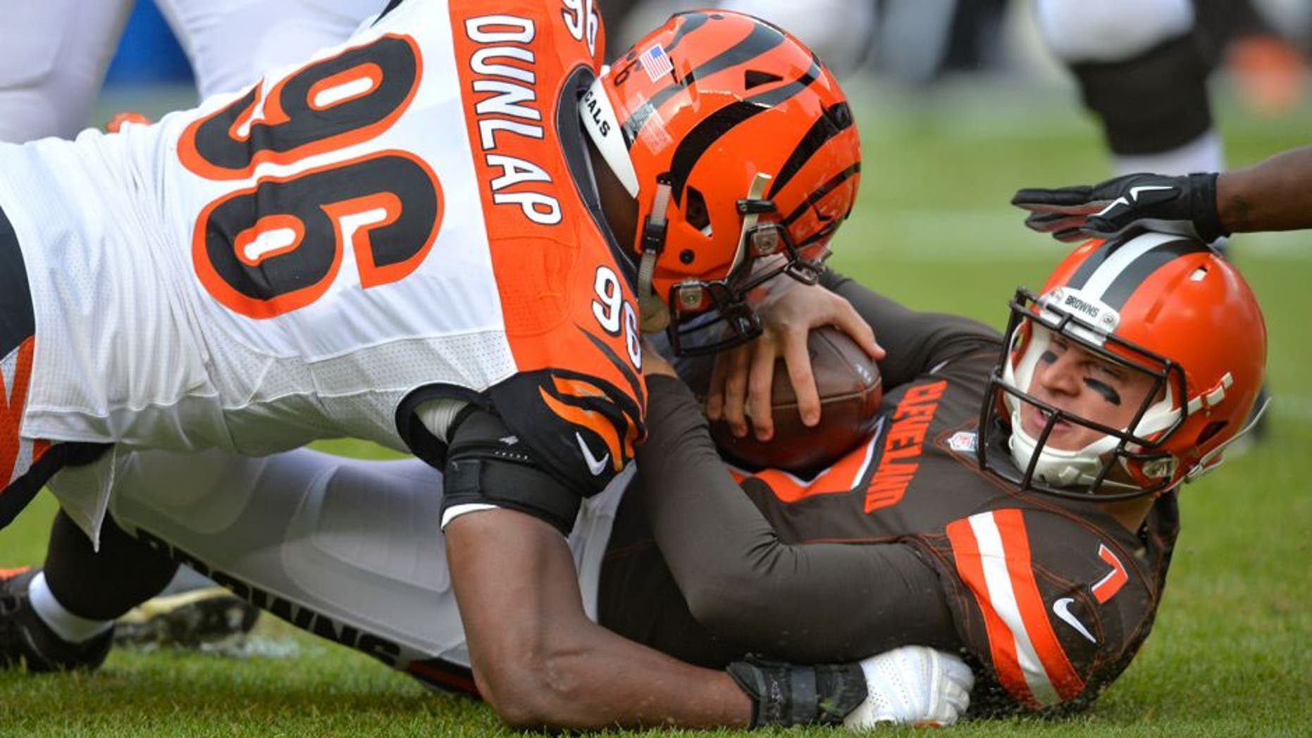 Cleveland Browns quarterback Austin Davis (7) is tackled by Cincinnati Bengals defensive end Carlos Dunlap (96) in the first half of an NFL football game, Sunday, Dec. 6, 2015, in Cleveland. (AP Photo/David Richard)