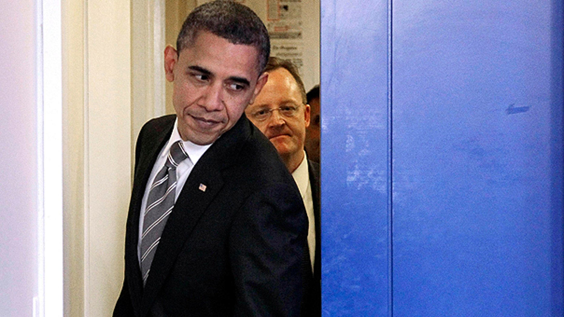 Dec. 7: President Obama, followed by White House Press Secretary Robert Gibbs, slides past the pocket door to the briefing room as he walks out to begin his news conference at the White House in Washington.