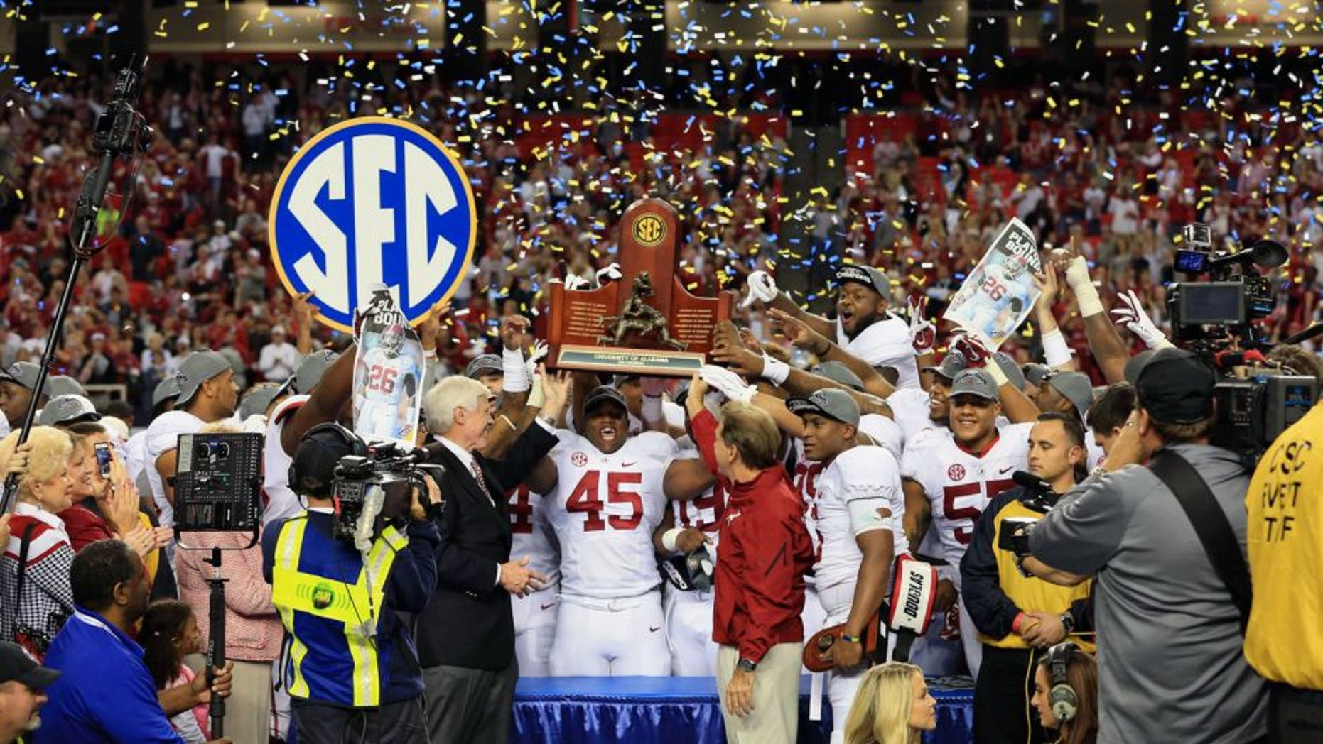 Dec 6, 2014; Atlanta, GA, USA; Alabama Crimson Tide head coach Nick Saban and his team celebrate with the trophy after the 2014 SEC Championship Game against the Missouri Tigers at the Georgia Dome. Alabama defeated Missouri 42-13. Mandatory Credit: Kevin Liles-USA TODAY Sports