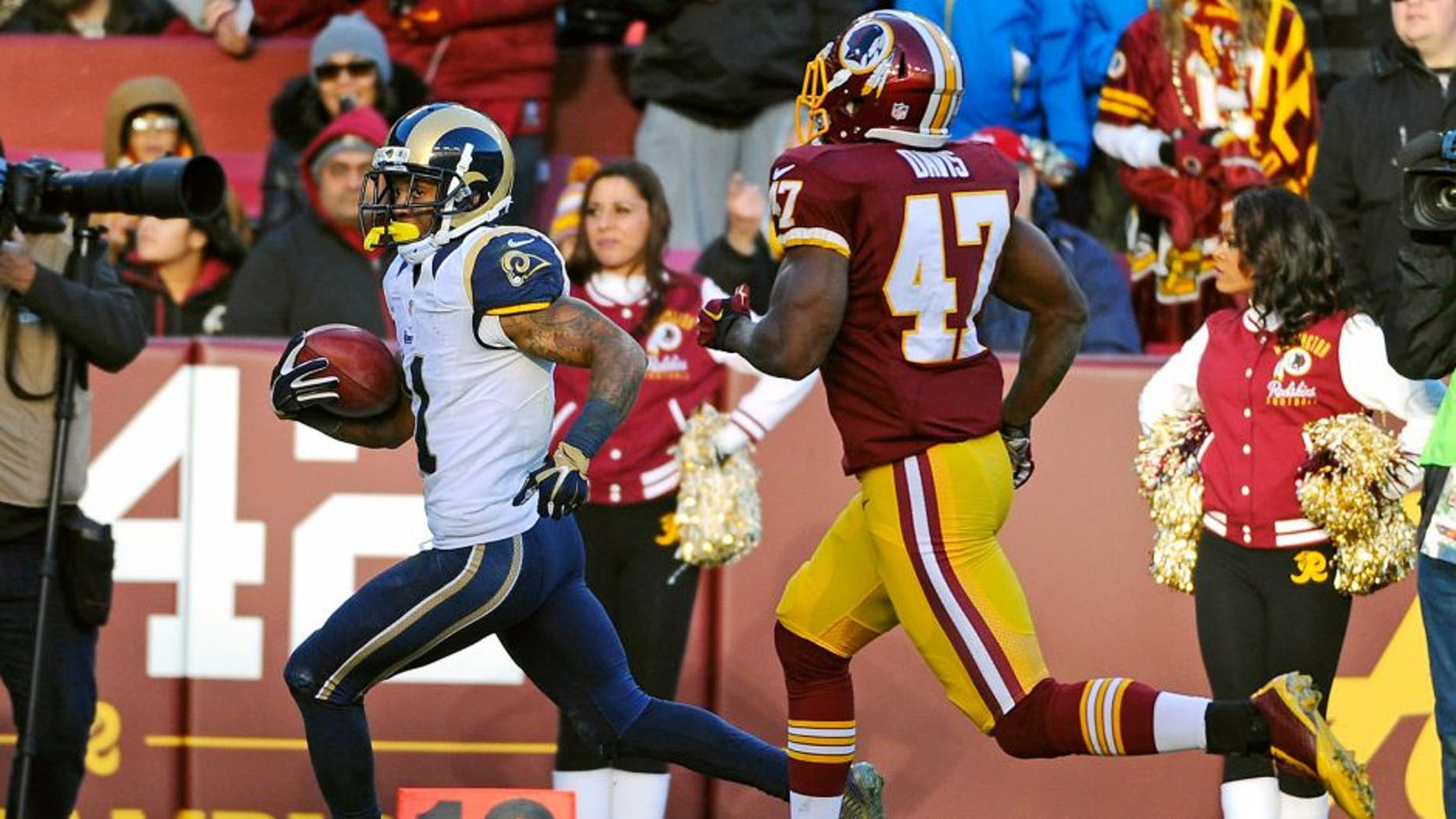 Dec 7, 2014; Landover, MD, USA; St. Louis Rams wide receiver Tavon Austin (11) returns a punt for a touchdown as Washington Redskins defensive back Akeem Davis (47) chases during the second half at FedEx Field. Mandatory Credit: Brad Mills-USA TODAY Sports