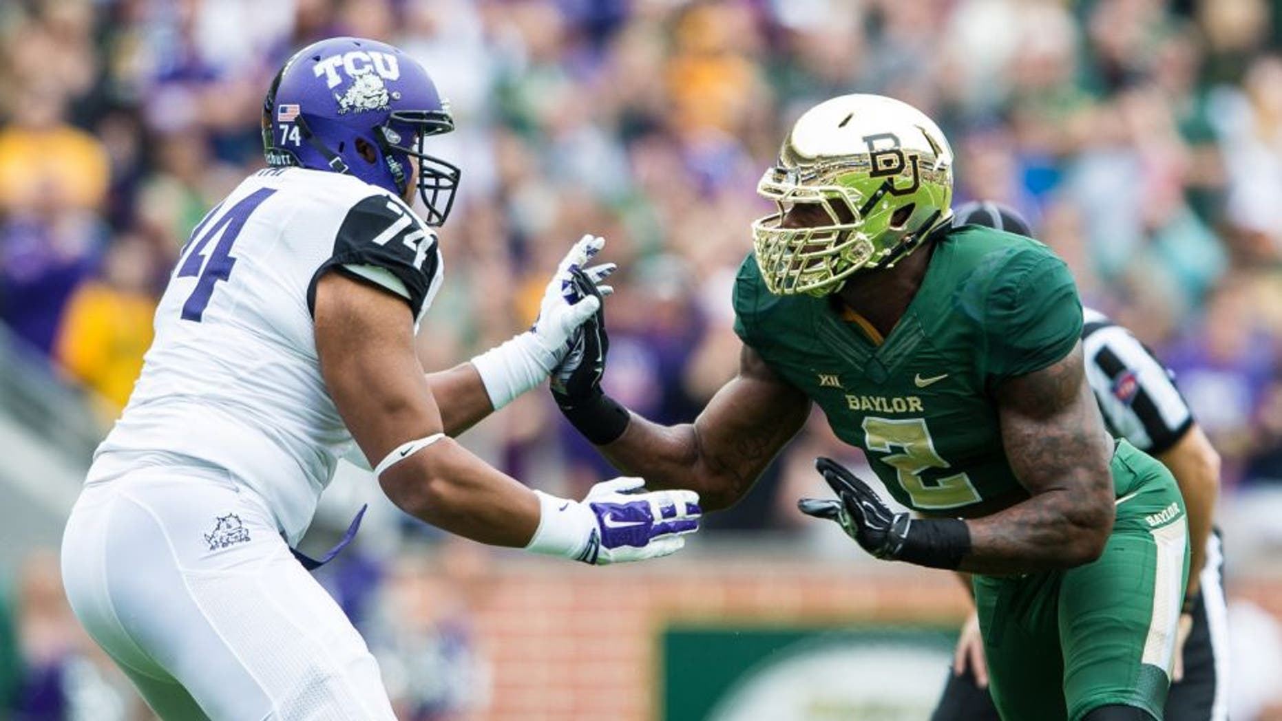 Oct 11, 2014; Waco, TX, USA; TCU Horned Frogs offensive tackle Halapoulivaati Vaitai (74) faces off against Baylor Bears defensive end Shawn Oakman (2) during the game at McLane Stadium. The Bears defeat Horned Frogs 61-58. Mandatory Credit: Jerome Miron-USA TODAY Sports