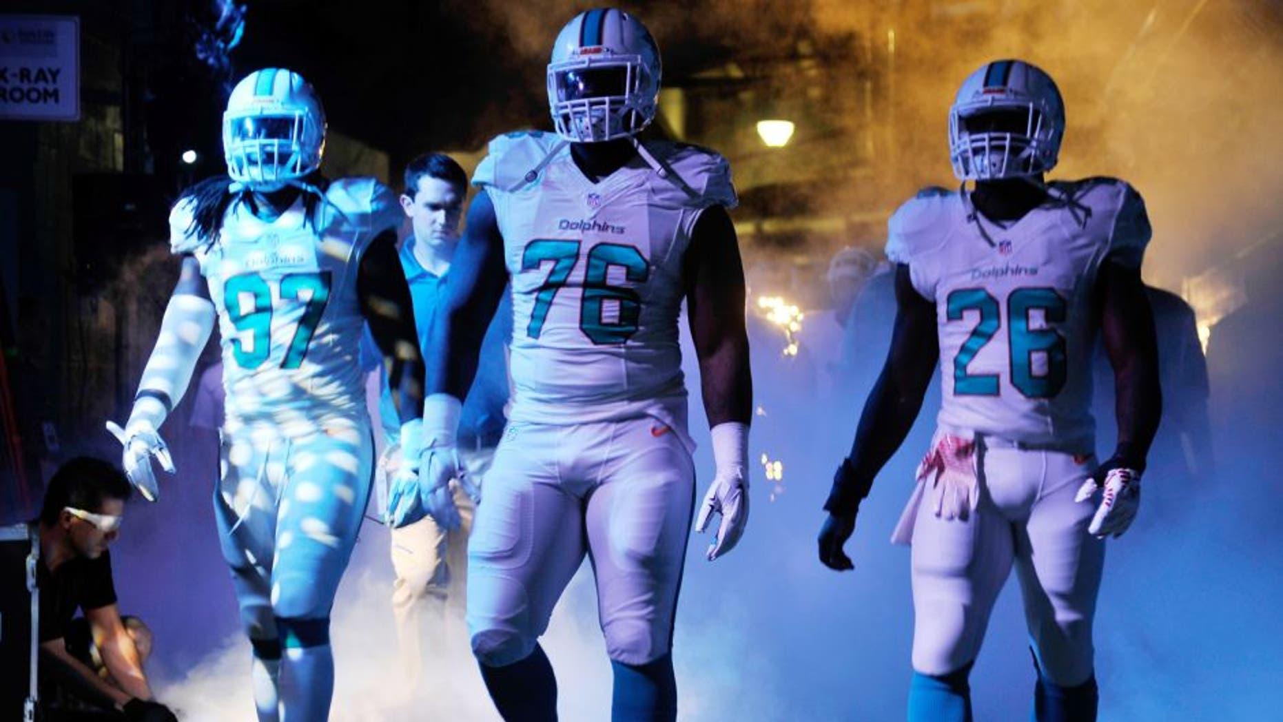 Dec 7, 2014; Miami Gardens, FL, USA; Miami Dolphins linebacker Kelvin Sheppard (left), defensive end Terrence Fede (center) and running back Knowshon Moreno (right) prepare to take the field before a game against the Baltimore Ravens at Sun Life Stadium. Mandatory Credit: Steve Mitchell-USA TODAY Sports