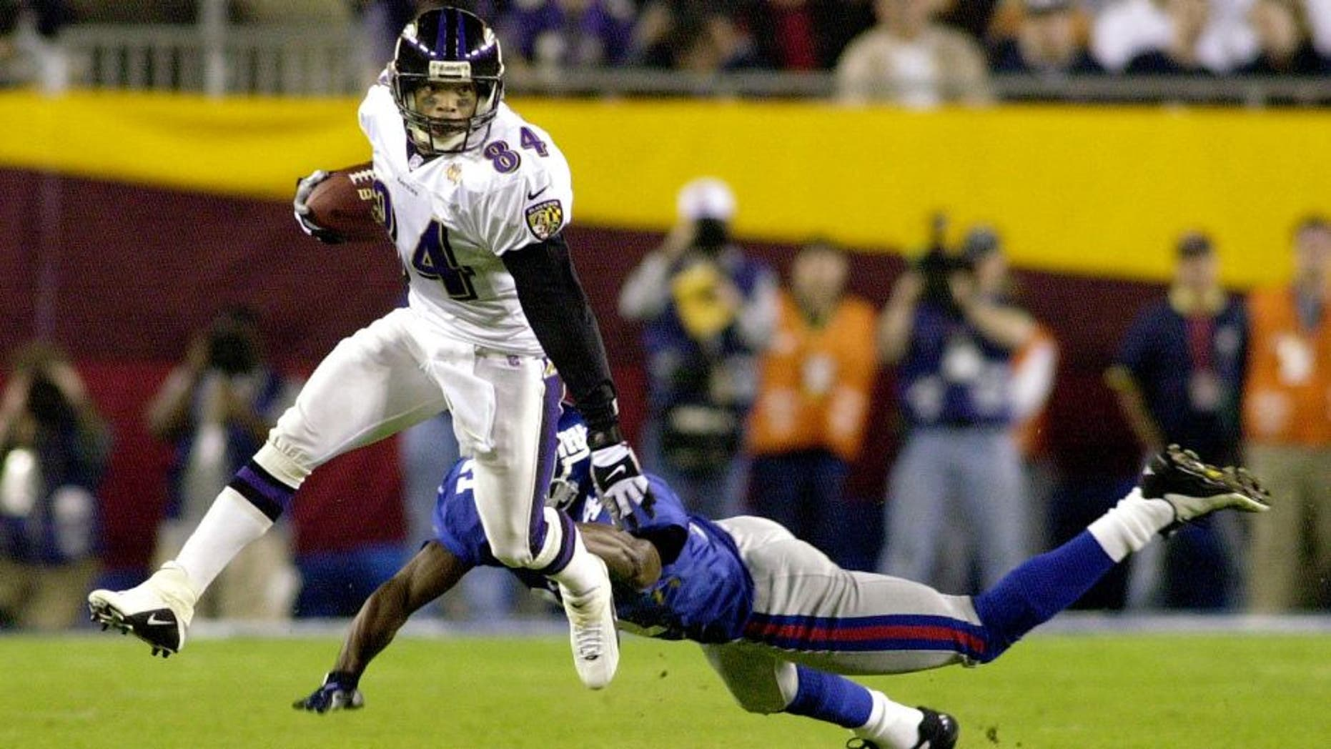 TAMPA, FL - JANUARY 28: Baltimore Ravens' wide receiver Jermaine Lewis (L) avoids an open field tackle by Dave Thomas of the New York Giant defender during first half action in Super Bowl XXXV 28 January, 2001, at Raymond James Stadium in Tampa, Florida. The New York Giants and the Baltimore Ravens are playing for the Vince Lombardi Trophy and the NFL championship. (Photo credit should read PETER MUHLY/AFP/Getty Images)