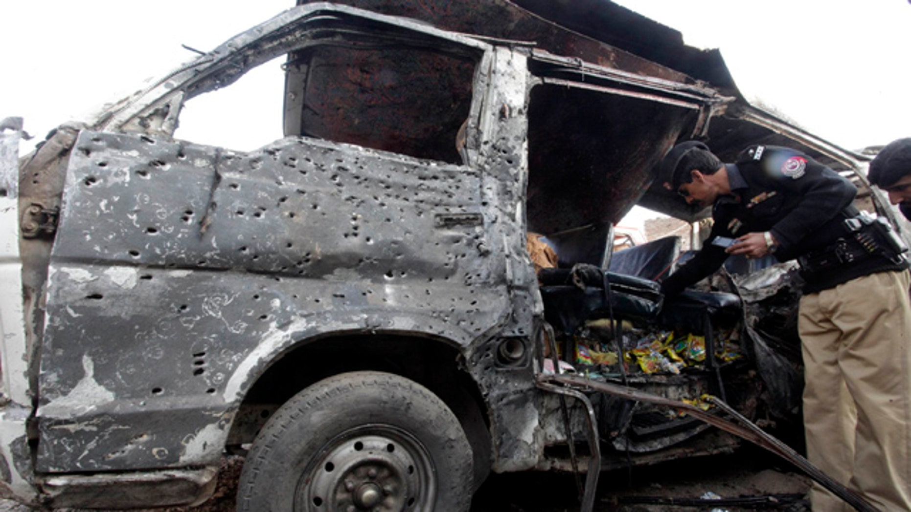Dec. 8: Pakistani security officials examine the vehicle targeted by a suicide attacker in Kohat, 37 miles south of Peshawar, Pakistan.