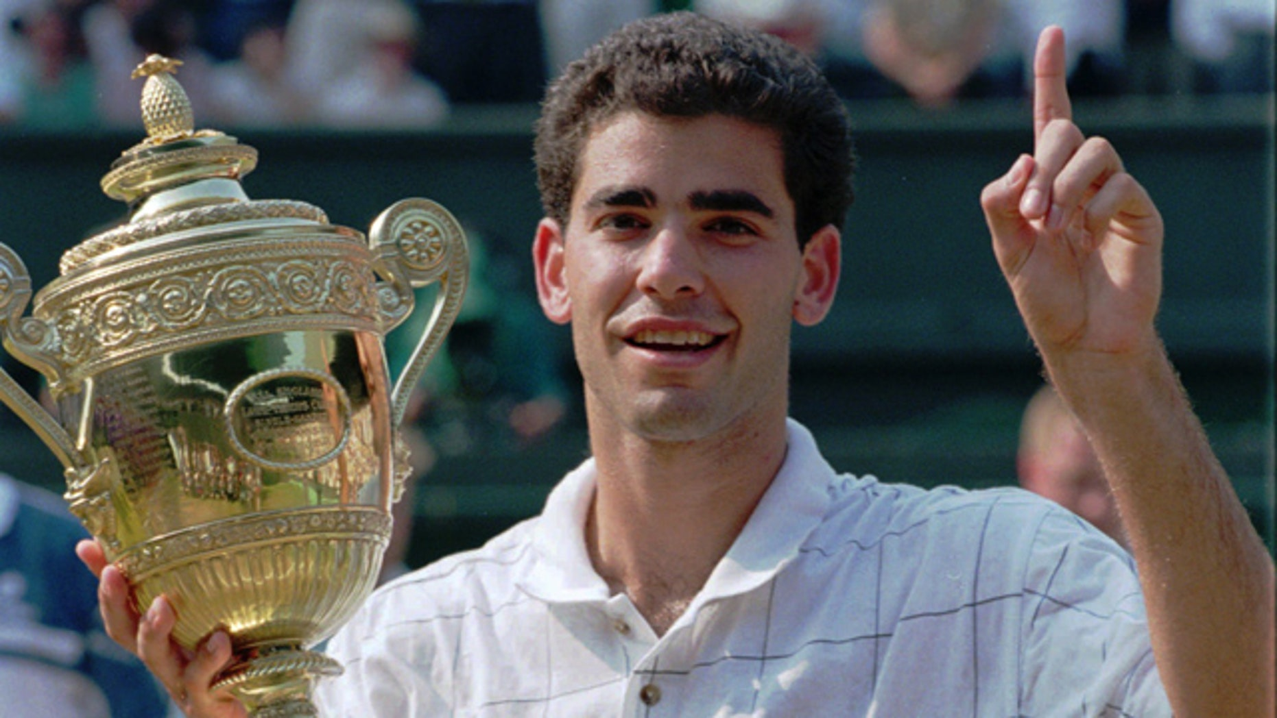 Pete Sampras indicates he is number one while holding his trophy after defeating Boris Becker to win the Men's Single's Final on Centre Court at Wimbledon, in this July 9, 1995 file photo.