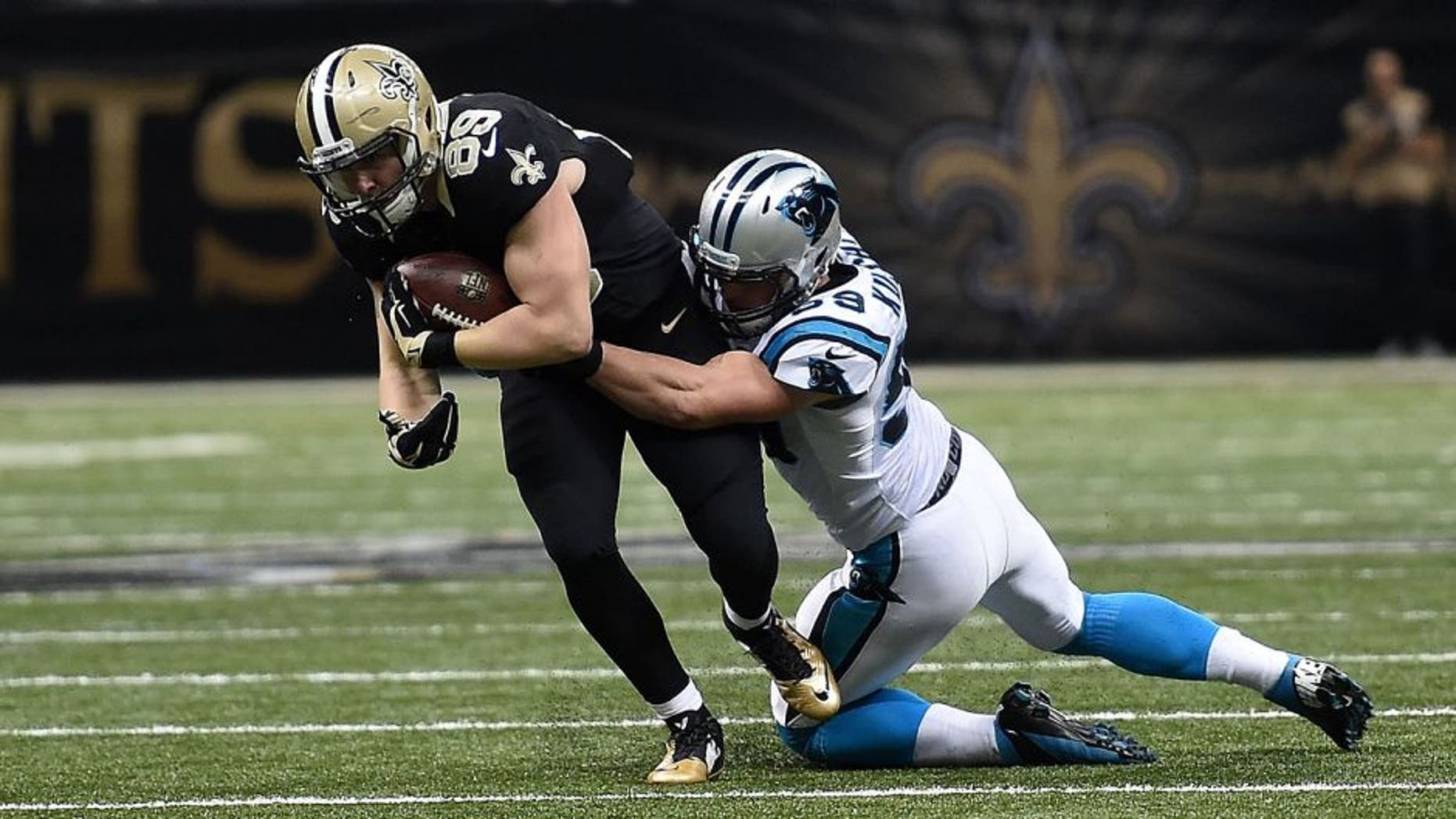 NEW ORLEANS, LA - DECEMBER 06: Josh Hill #89 of the New Orleans Saints is brought down by Luke Kuechly #59 of the Carolina Panthers during a game at the Mercedes-Benz Superdome on December 6, 2015 in New Orleans, Louisiana. Carolina defeated New Orleans 41-38. (Photo by Stacy Revere/Getty Images)